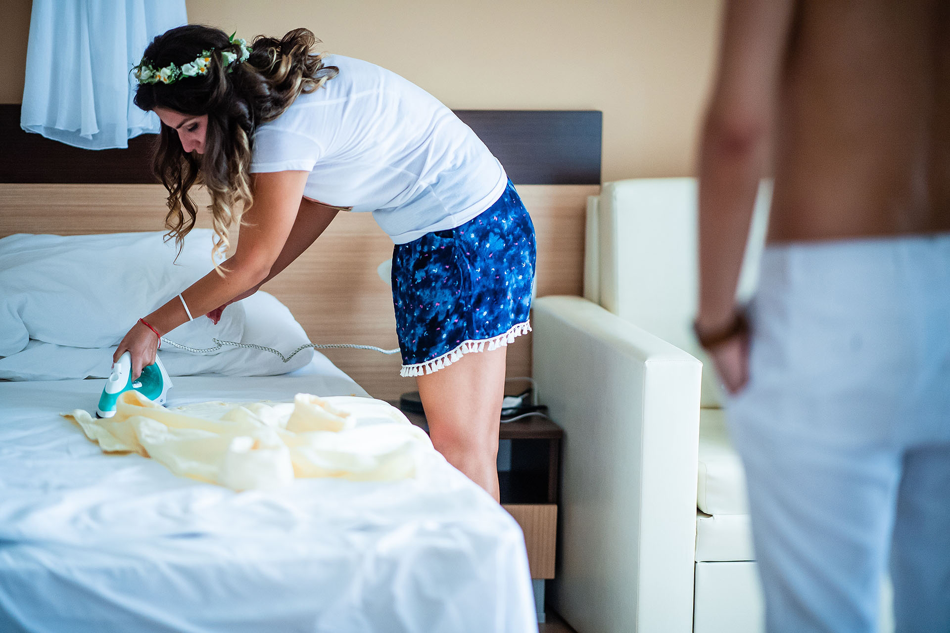 Sozopol, Bulgaria Elopement Image | The bride touches up the groom's wedding shirt with a steam iron