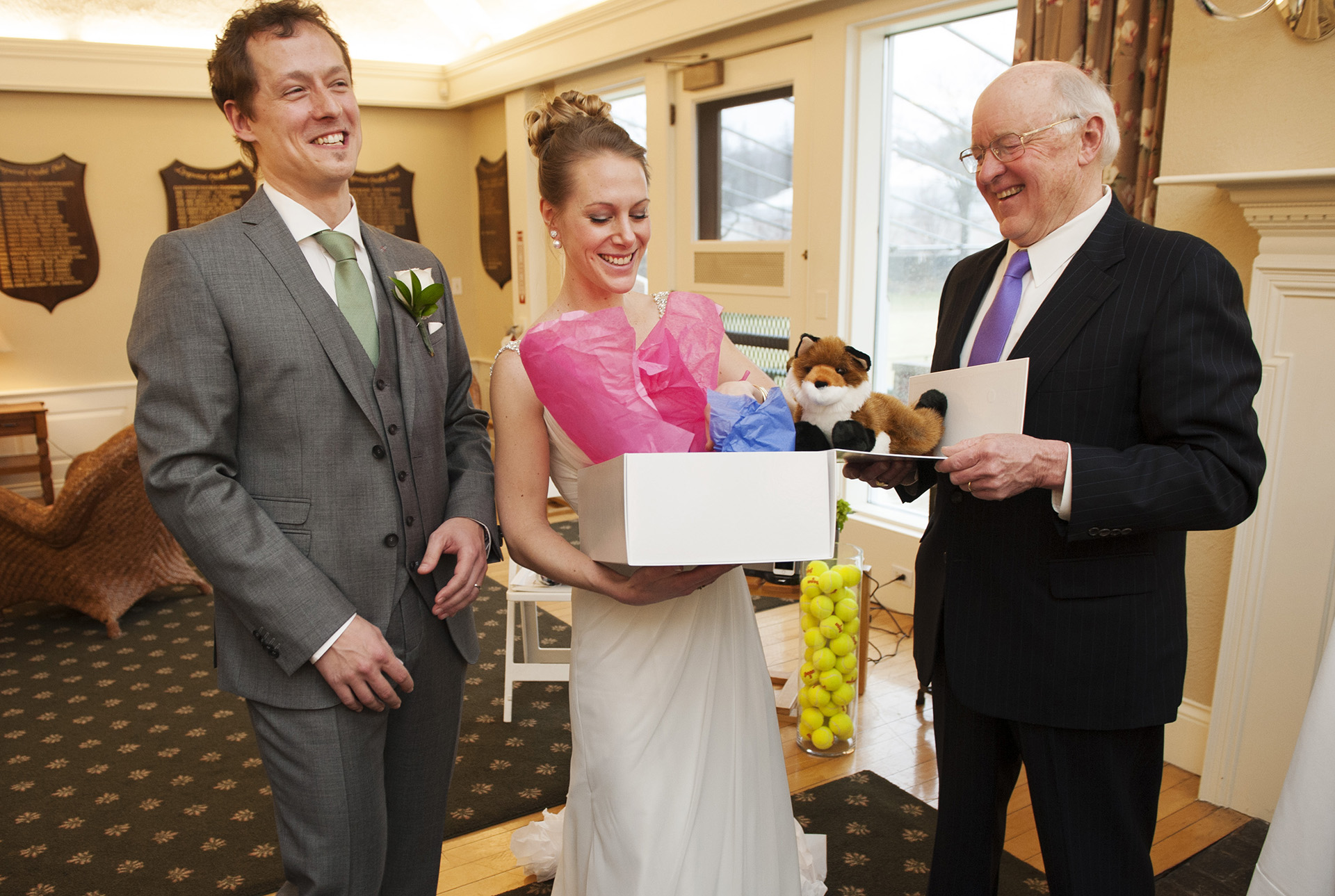 MA Elopement Photographer | The newlyweds laugh as they open their officiant's gift to them
