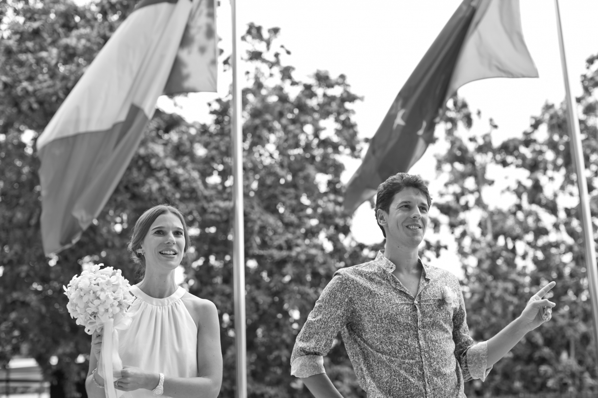 Singapore Elopement Images | The young couple stand together beneath the flags of France and Singapore