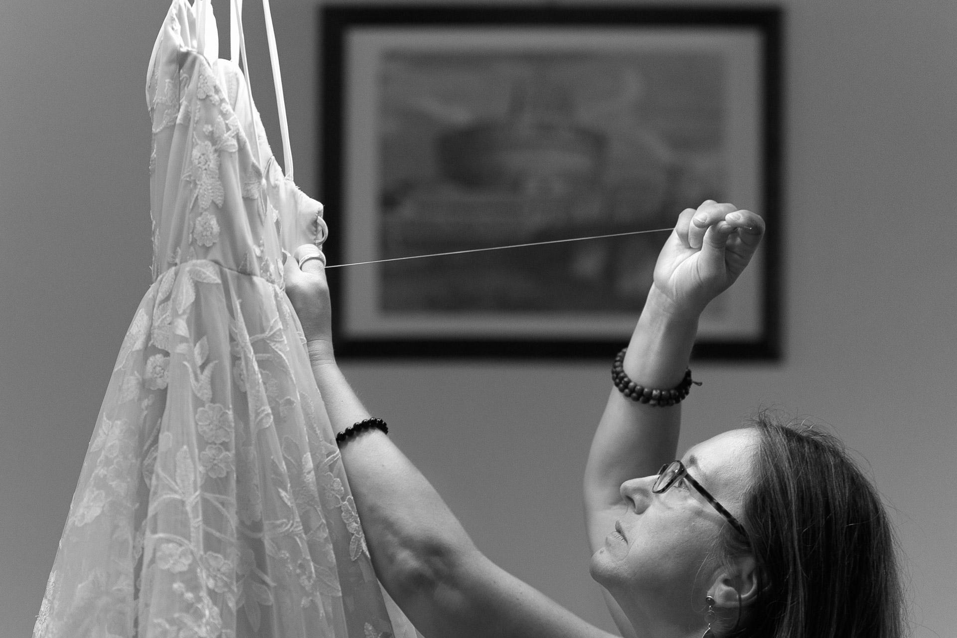 Arezzo, Toskana, IT Elopement Foto | Die Mutter des Bräutigams repariert das Kleid der Braut