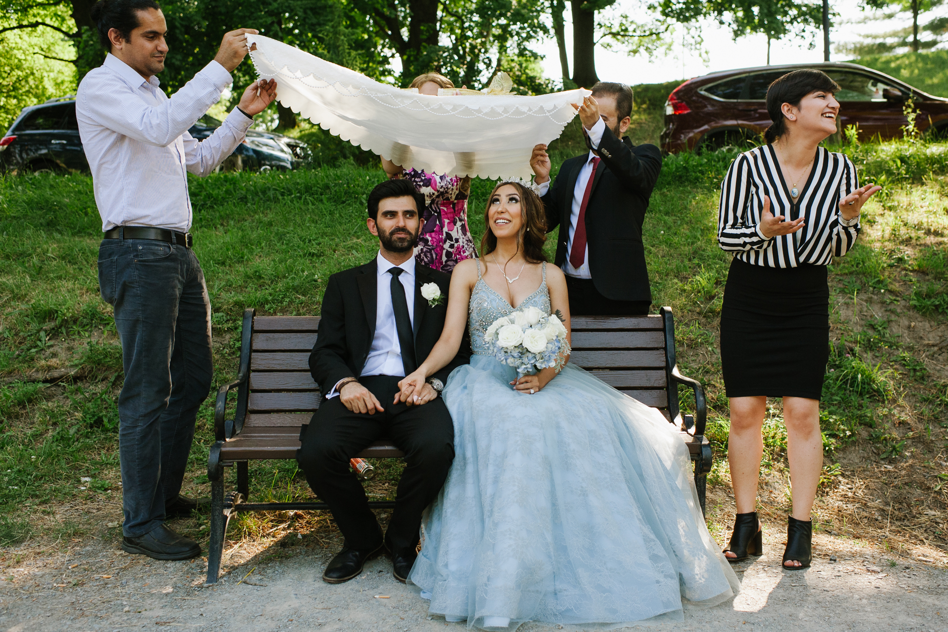 New York Wedding Elopement Photography | on a park bench as friends hold a fabric over them while sugar is sprinkled on the fabric