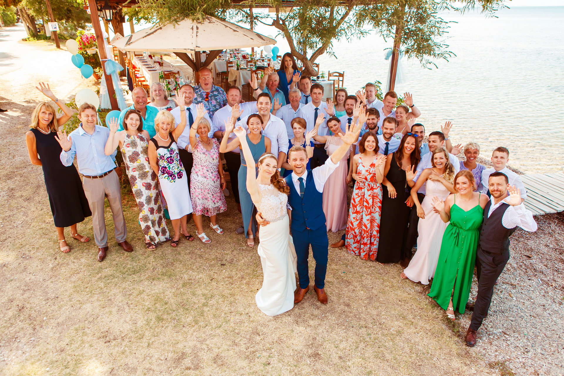 Greece Beach Elopement Portrait | The entire party joins the jubilant bride and groom
