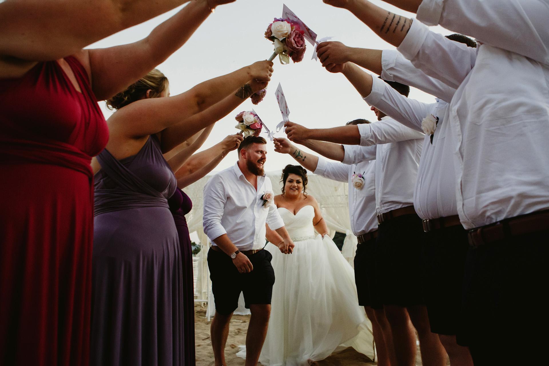 Fotografía de bodas en Billy's Beach, Fethiye, Mugla, Turquía | las damas de honor y los padrinos de boda hicieron un pasillo para la entrada de la pareja