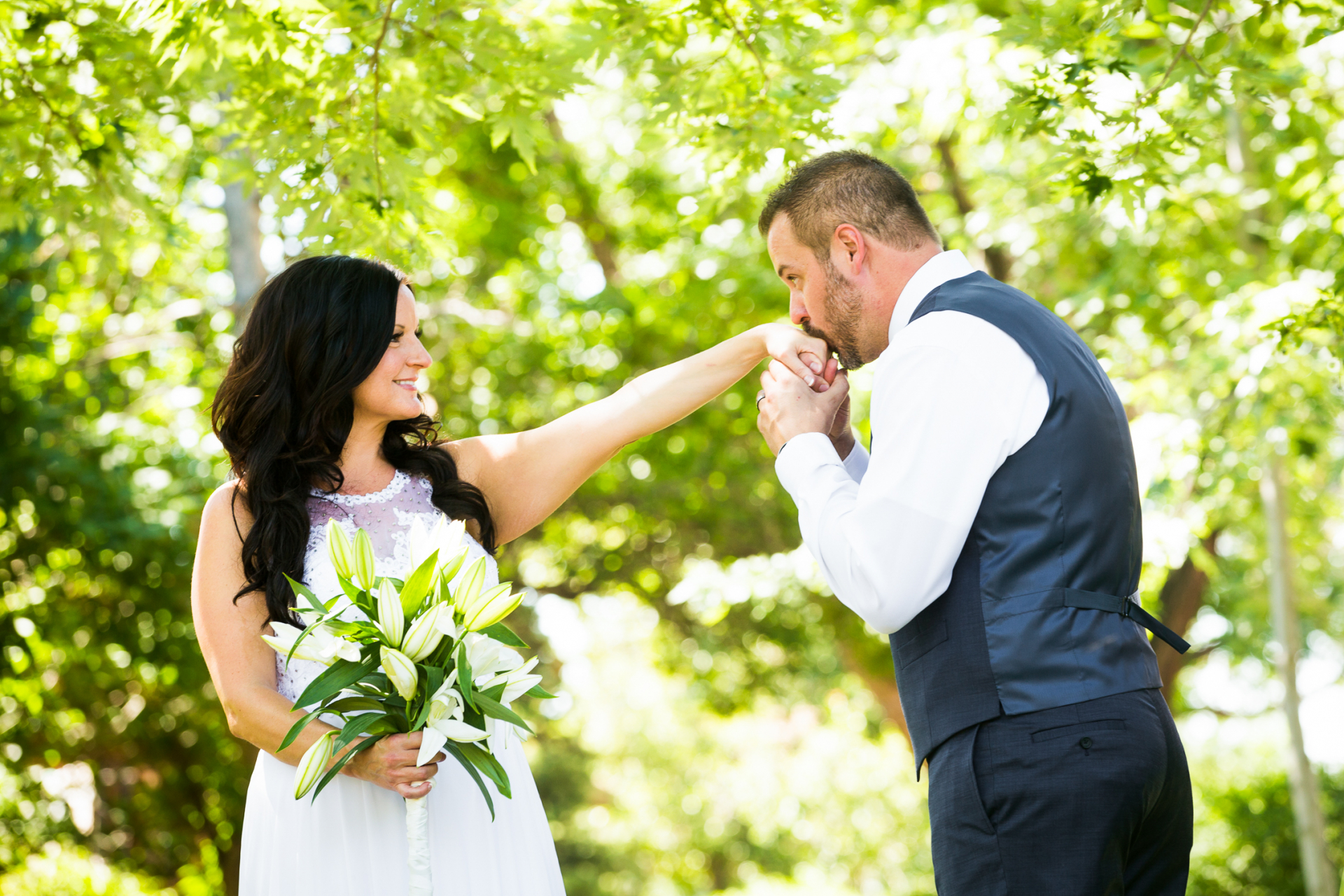 CO Wedding Couple Portrait - Elopement Images | the groom kisses his new wife's hand in a shady spot in their backyard