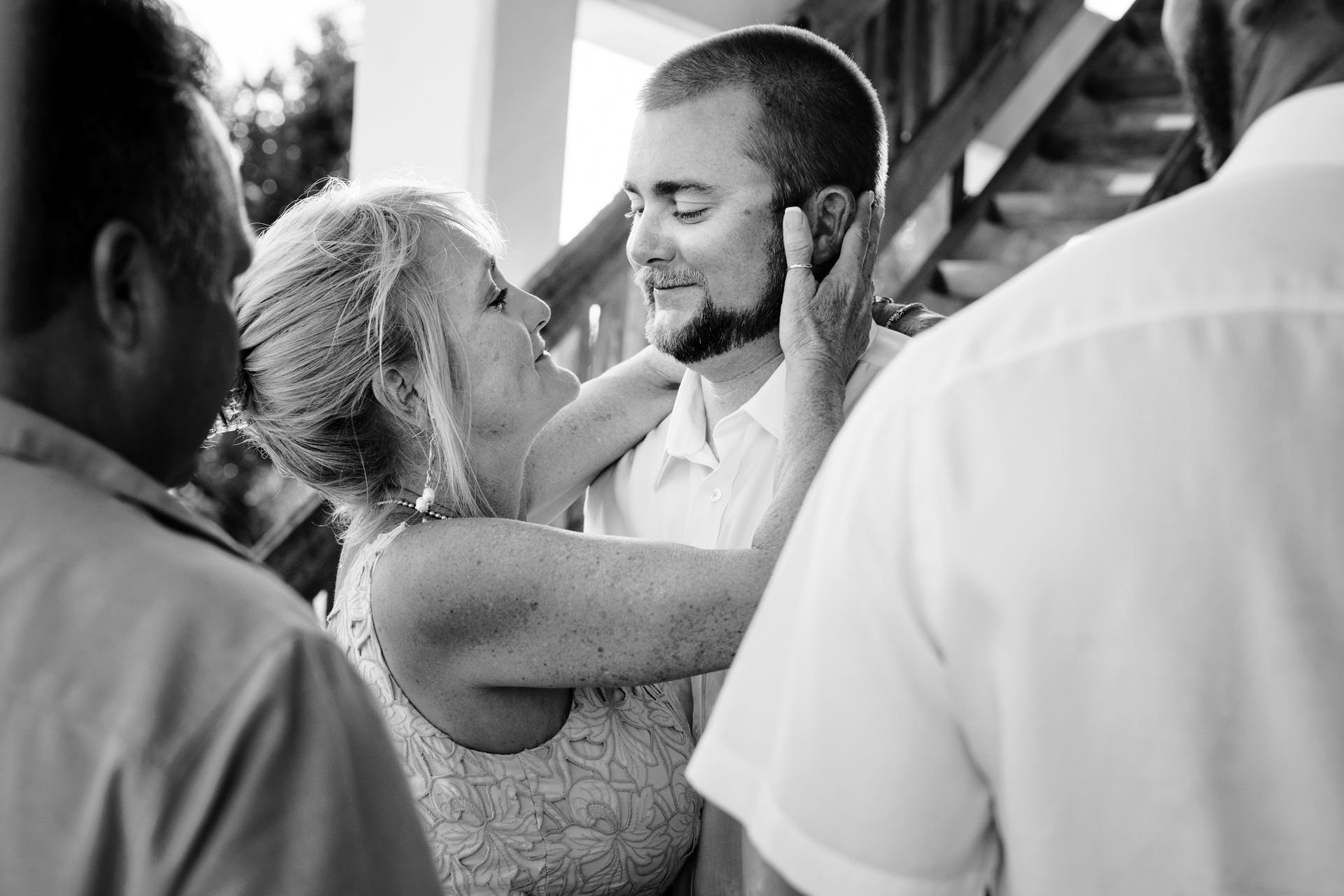 Florida Keys Elopement Photo - Groom Getting Hug Picture | The groom embraces his mother as she cups his cheeks