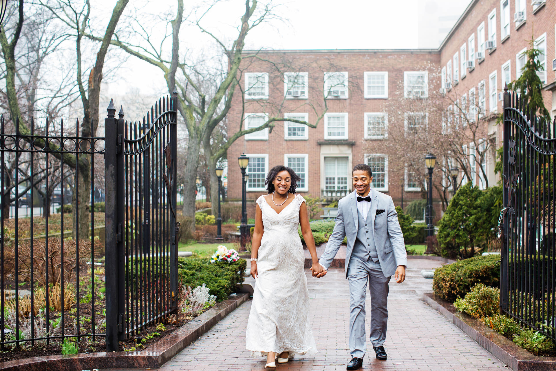 Queens Borough Hall Gardens Couple Wedding Portrait | The smiling couple strolls through the Queens Borough Hall garden