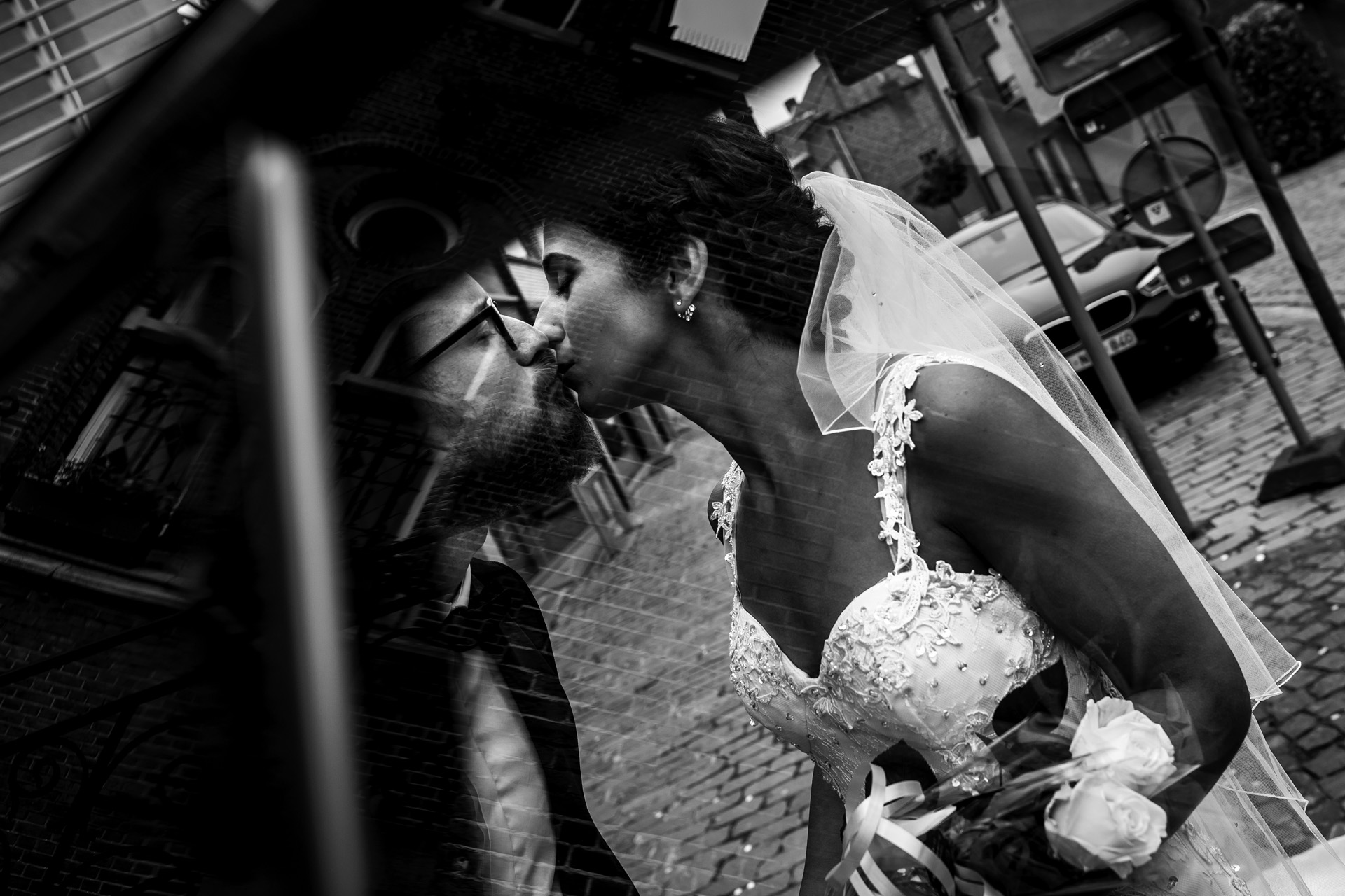 Antwerp Elopement Photo | Through the reflection in the car window we can see the bride and groom sharing a kiss