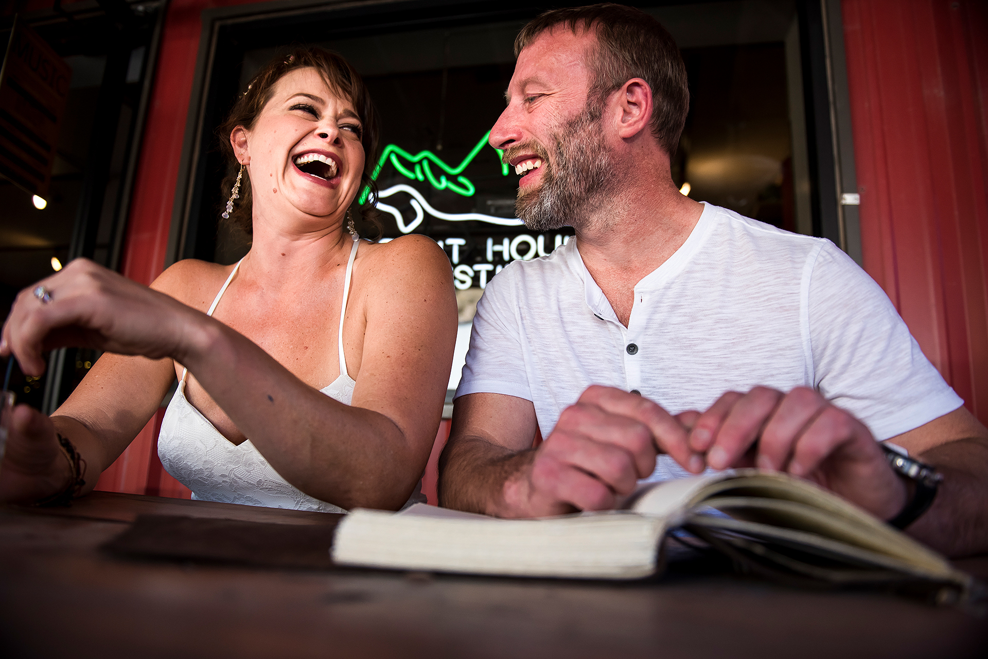 Estes Park, Colorado Elopement Picture at Spirit Hound Distillers | the bride and groom sit together outside a restaurant enjoying each other's company