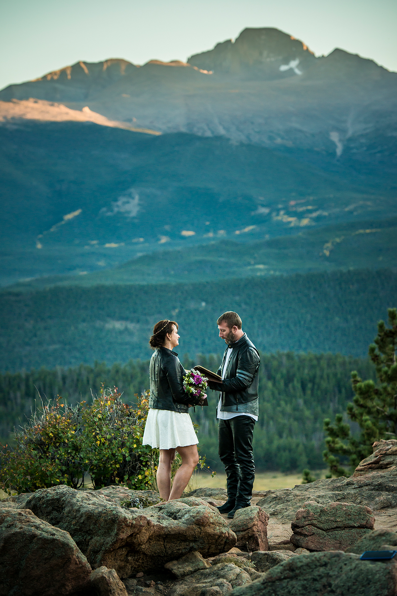 Colorado Adventure Wedding Ceremony Image | the groom reads his vows as the two of them stand on a cliff in Estes Park