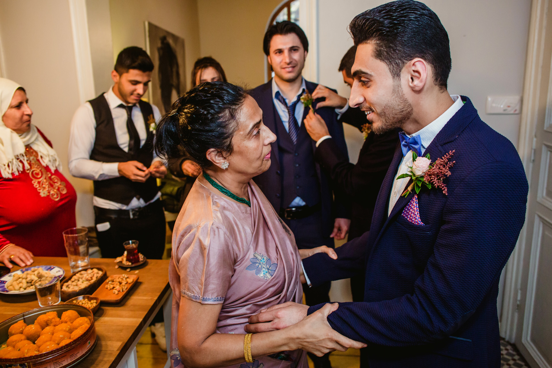 Istanbul Elopement Home Party Photo | the bride's mom pulls her new son-in-law aside to give him her well-wishes