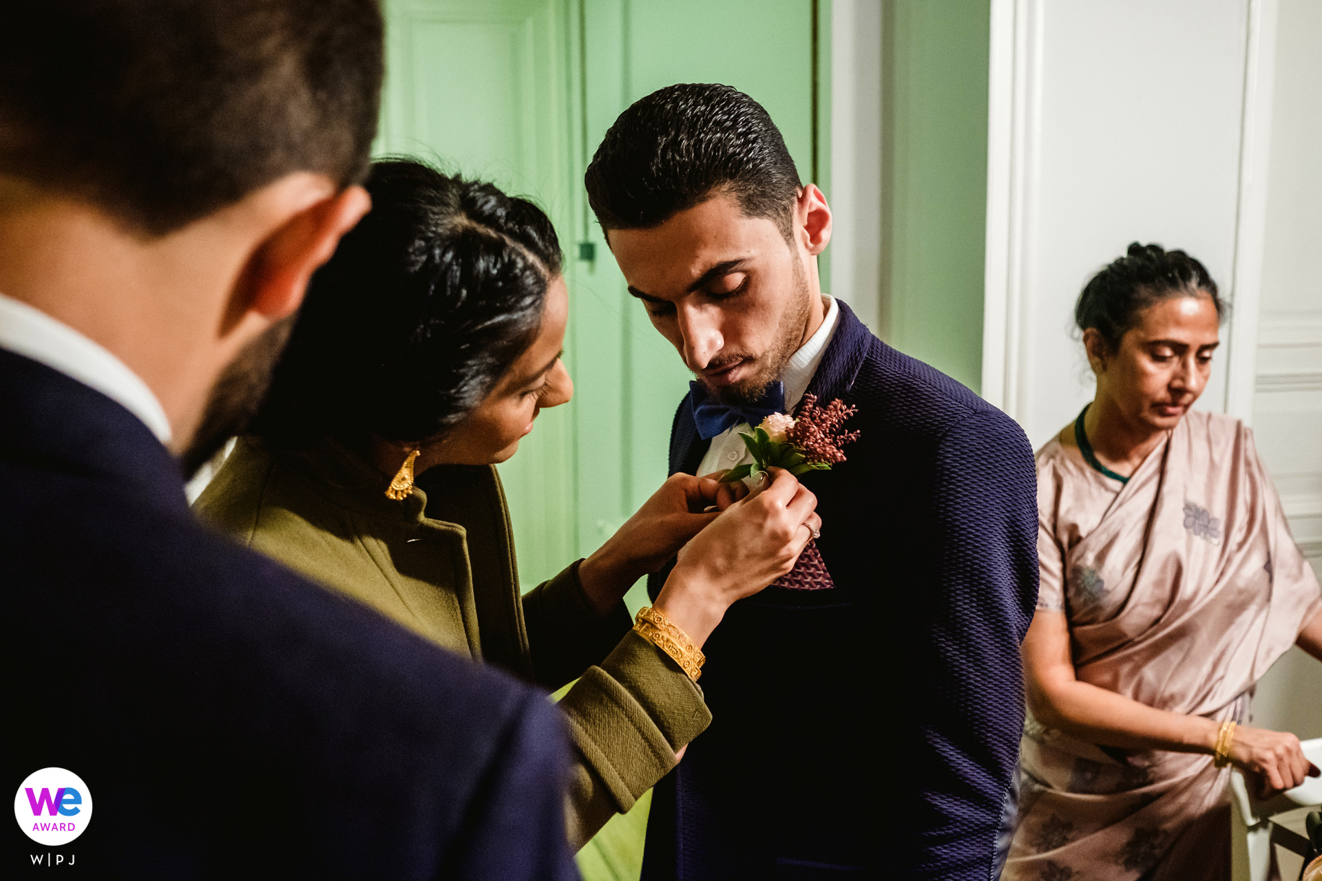 Cihangir, Istanbul, Turkey Elopement Photographer | the bride helps the groom prepare by fastening a boutonniere to his lapel as he watches
