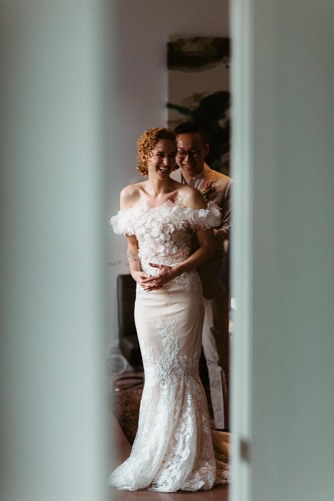 LA photo de couple de mariage | le marié aide la mariée avec sa robe avant la cérémonie