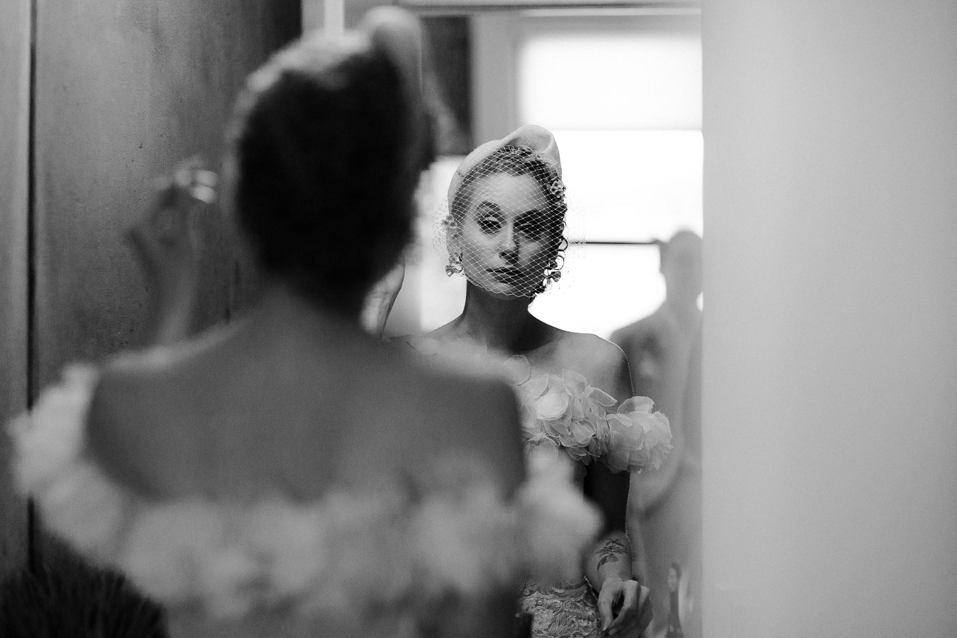 LA mariée se prépare pour la fuite Photo | La mariée se regarde dans le miroir et ajuste son voile