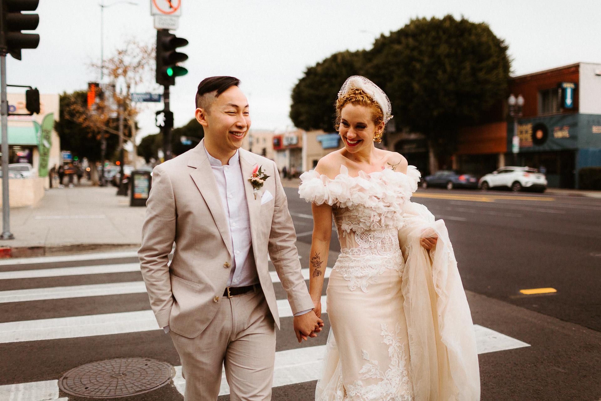 Photo d'un couple en fuite dans le sud de la Californie | Après la cérémonie, les mariés se promènent main dans la main dans les rues de LA