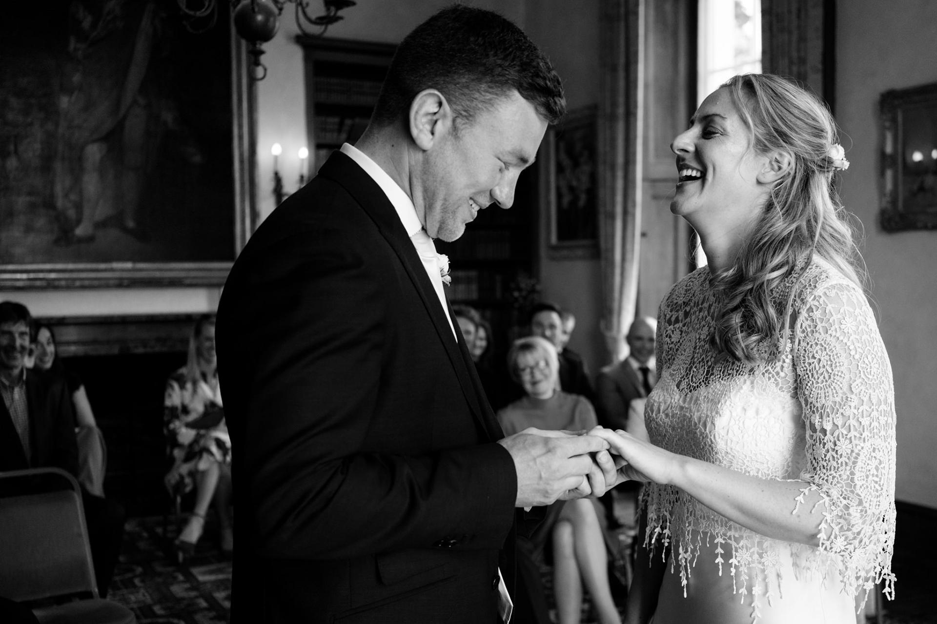Devon Wedding Ceremony Photographer | the bride smiles and laughs as the groom puts her ring on her finger