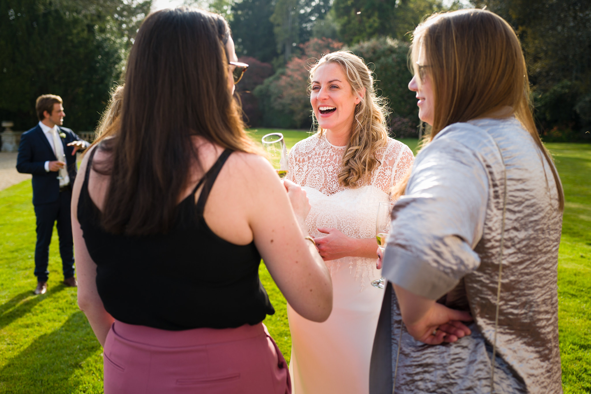 UK Elopement Bride w/ Friends Picture | The party has moved outside into the bright, warm sunlight