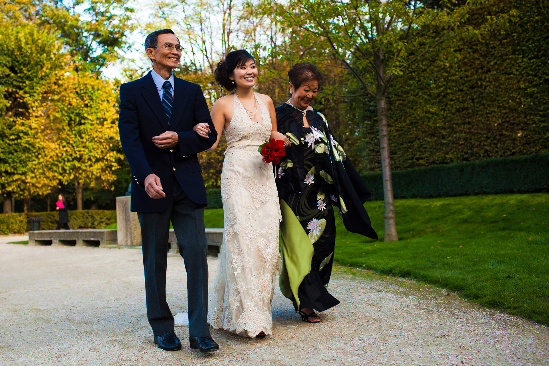 Paris France Elopement Ceremony Picture | The bride, wearing a lace gown, walks down a gravel path through greenery toward the ceremony