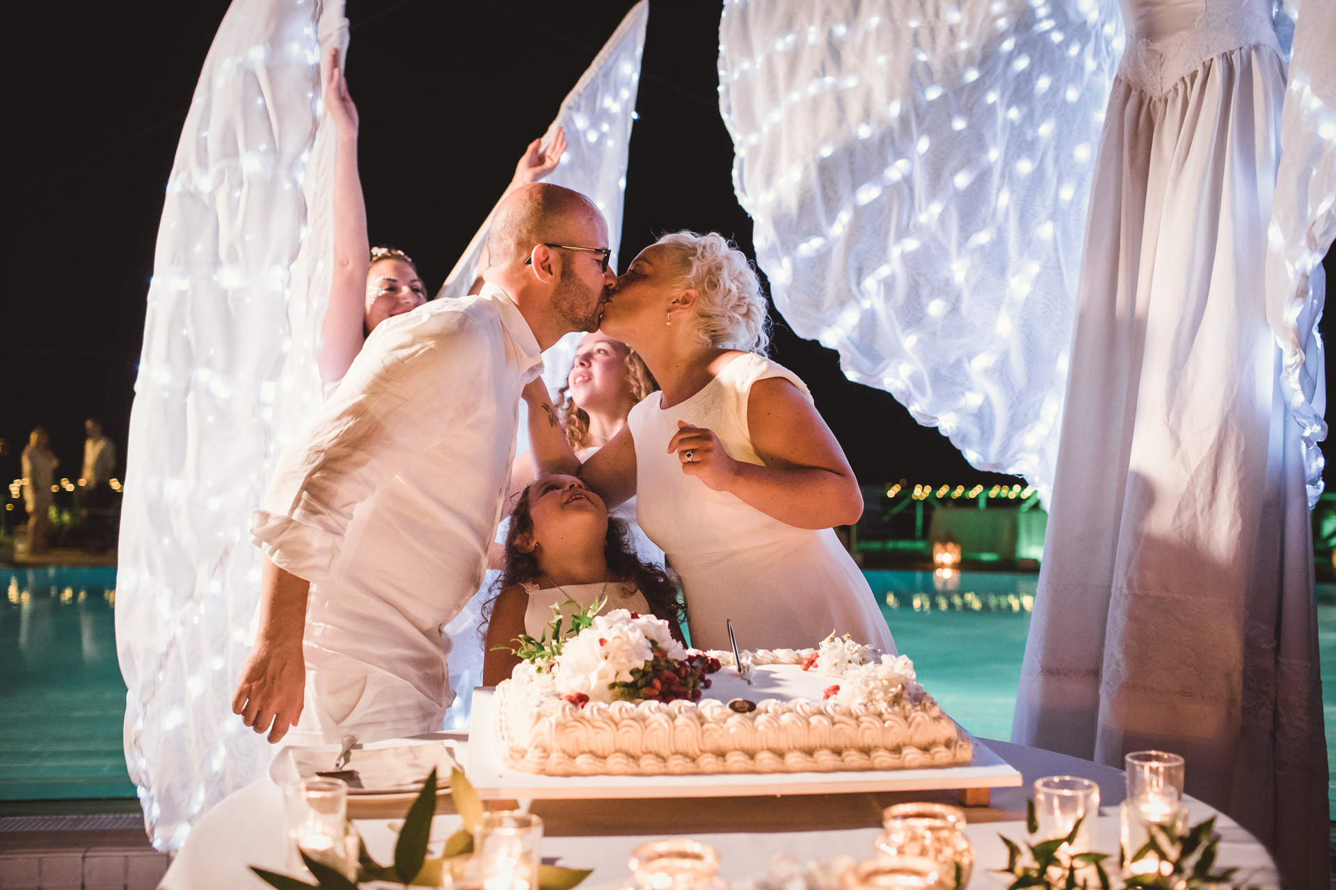 Italy Elopement Image from Da Gelsomina - Maresca | the couple shares a kiss over their wedding cake