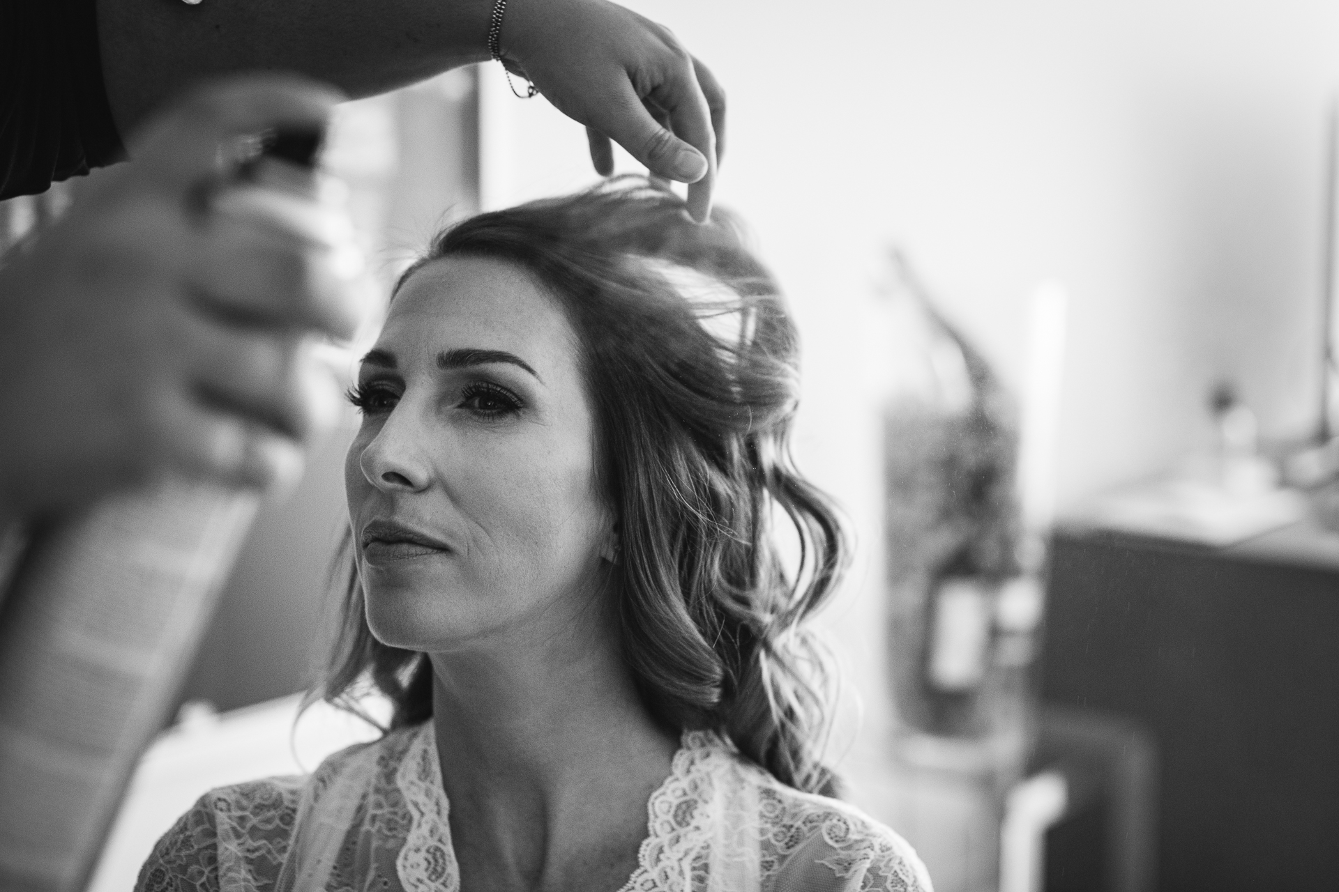 Switzerland Elopement Photo of Bride | The bride sits patiently as the hairdresser adds a bit of hairspray
