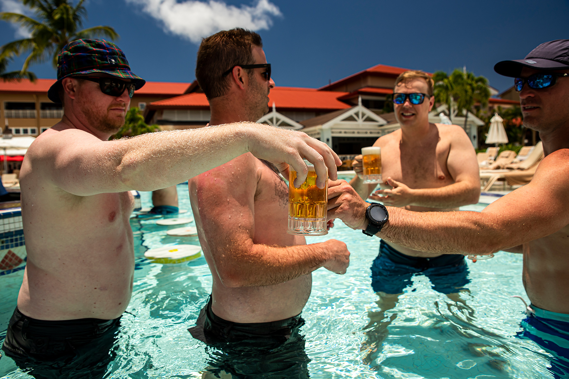 St. Lucia Elopement Fun Image | groom and groomsmen hang out and drink beer in the pool