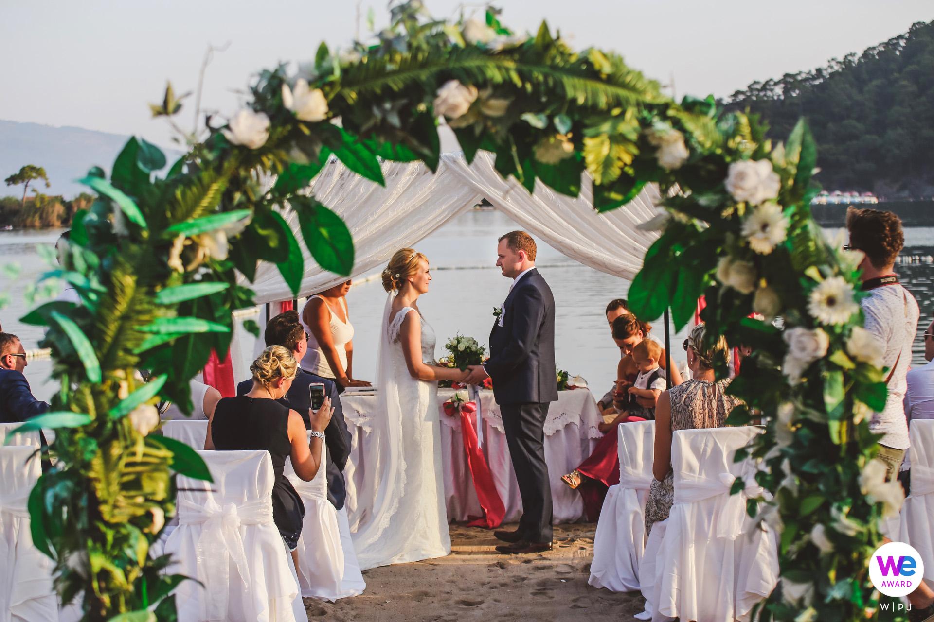 Sugar Beach Club, Oludeniz, Fethiye, Turquía Elopement Fotógrafo | La novia y el novio estaban parados juntos en el altar rodeados de sus familiares y amigos más cercanos.