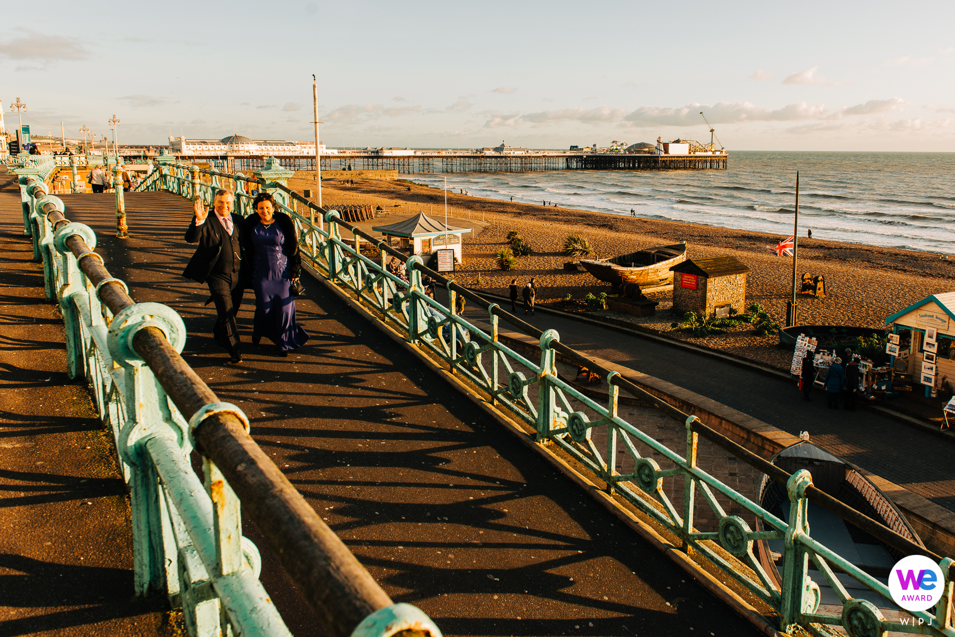 Brighton Seafront, UK Elopement Portrait of the Couple | the bride and groom as they walked toward the beach in the late afternoon winter sun,