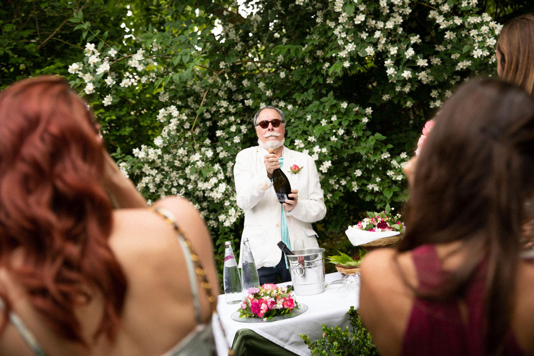 Italie Elopement Garden Cérémonie Photographie à la forêt de chênes verts | le père du marié a débouché une bouteille de prosecco.