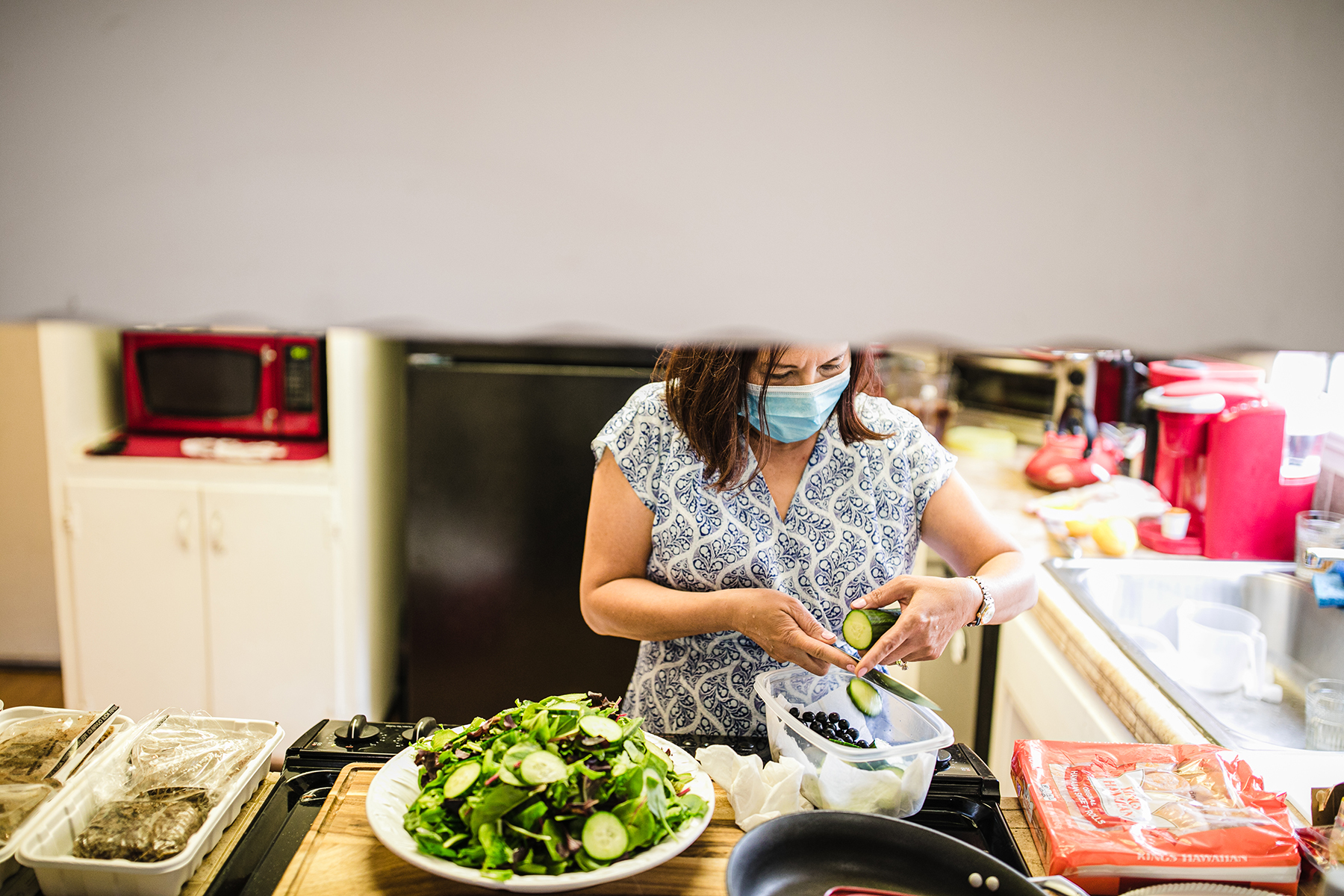 Image from an At-Home Elopement in Antioch, California | In the kitchen, the bride's mother helps out by preparing dinner