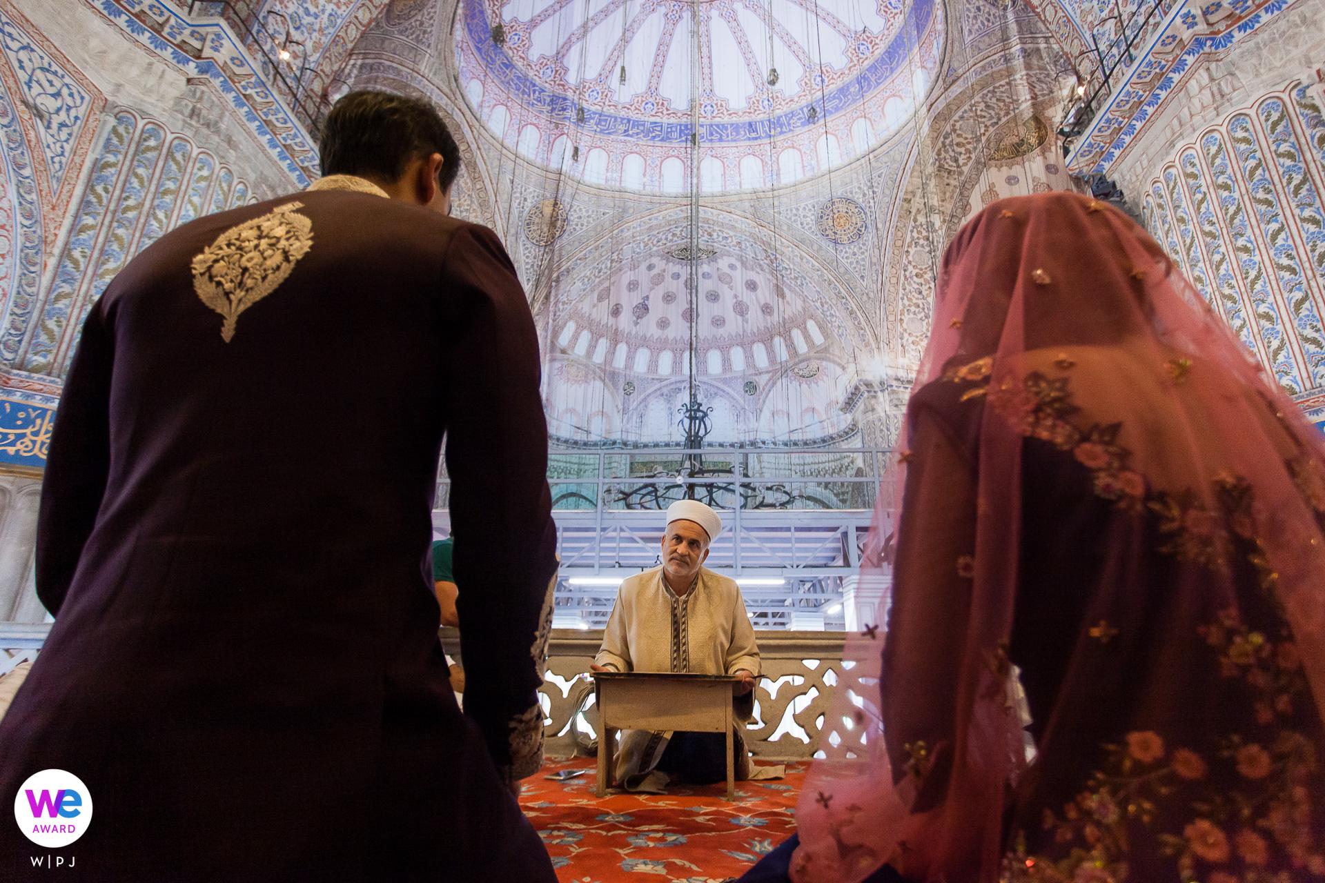 Blaue Moschee, Istanbul, Türkei Elopement Fotografie | Der Imam führt eine muslimische Hochzeitszeremonie durch, während Braut und Bräutigam zuhören
