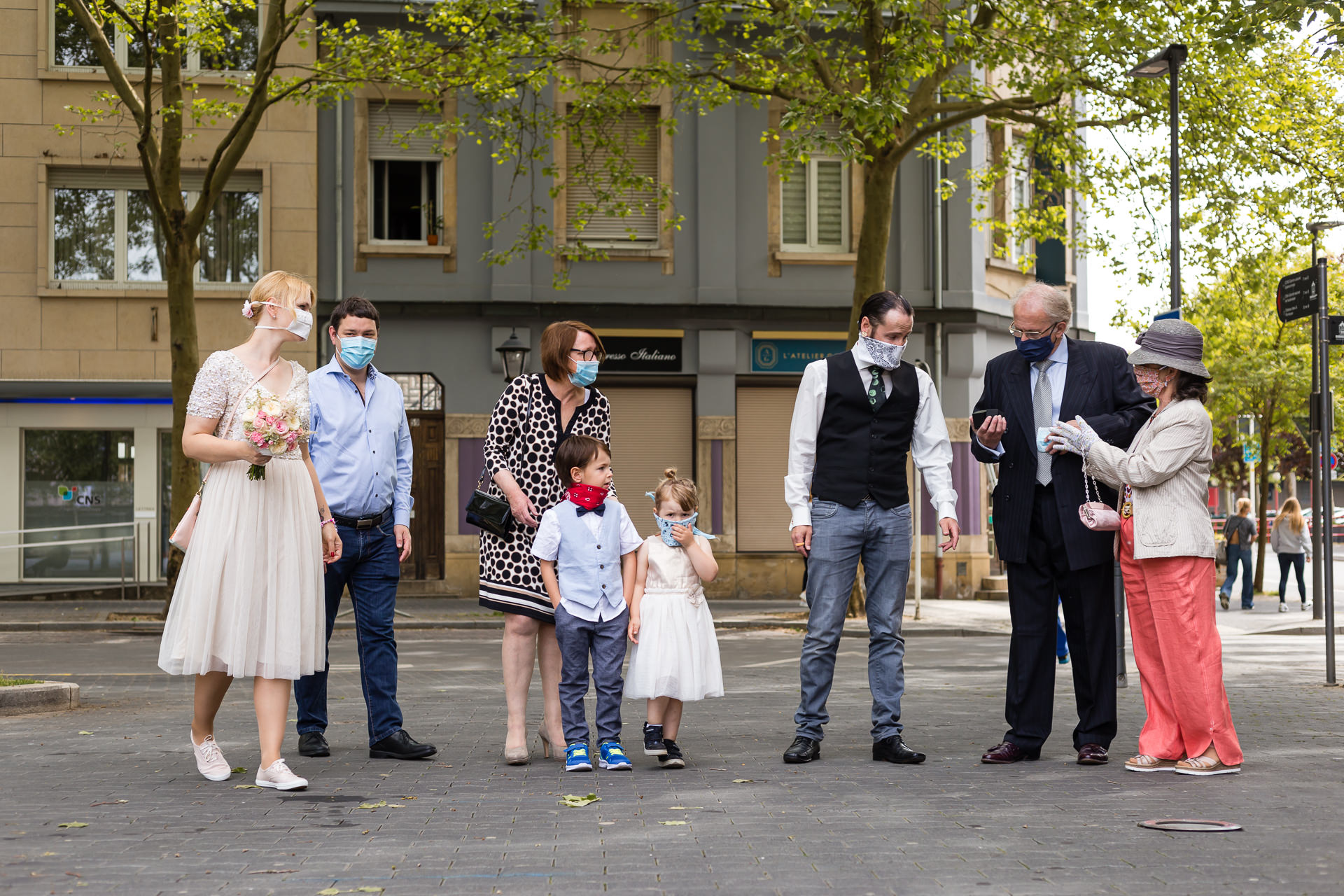 Dudelange City Hall of Luxembourg Elopement Photos | The bride, groom, and their families meet outside before the ceremony wearing face masks