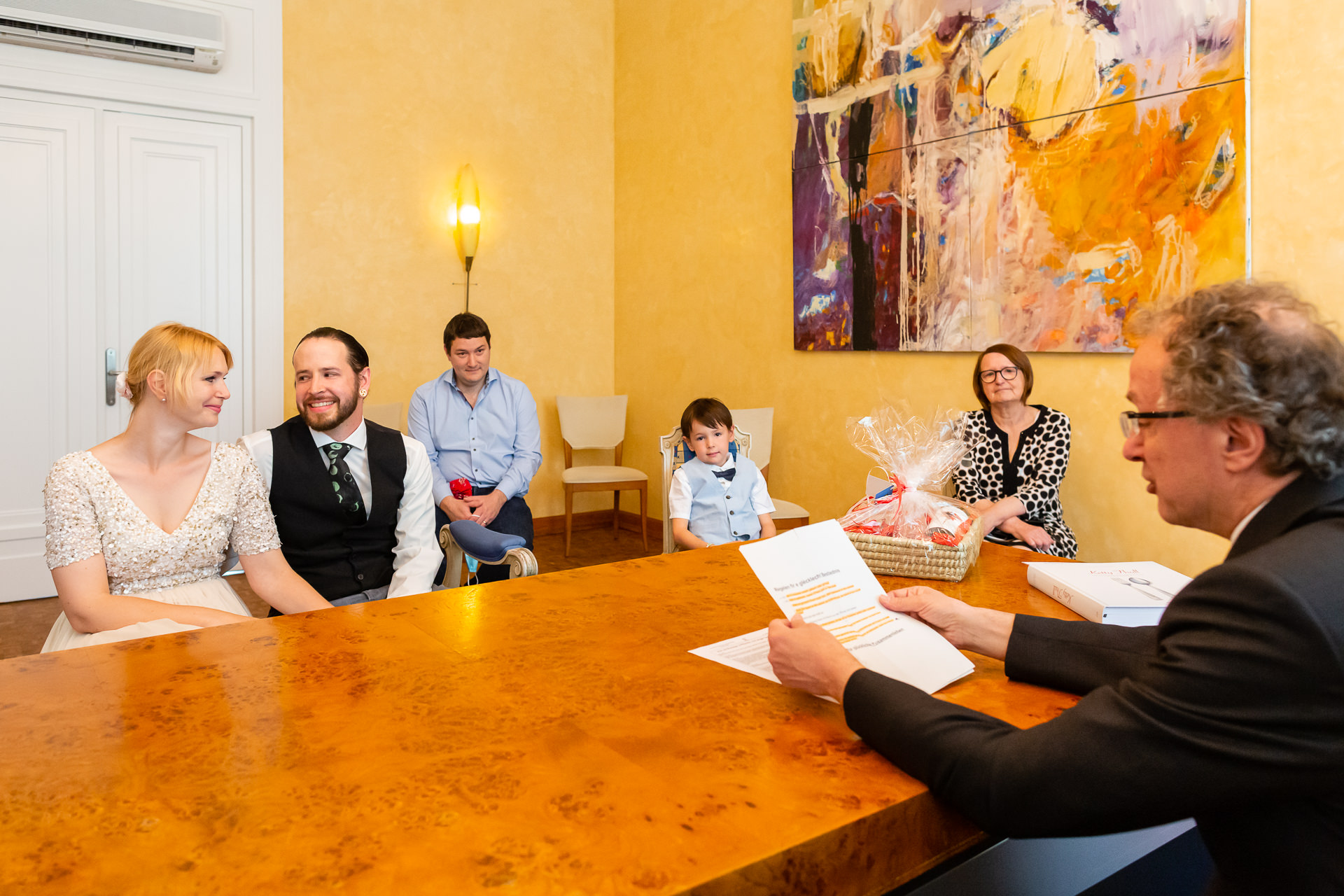 City Hall Pictures - Luxembourg Elopements | The couple sit together at a table in a bright room during the ceremony