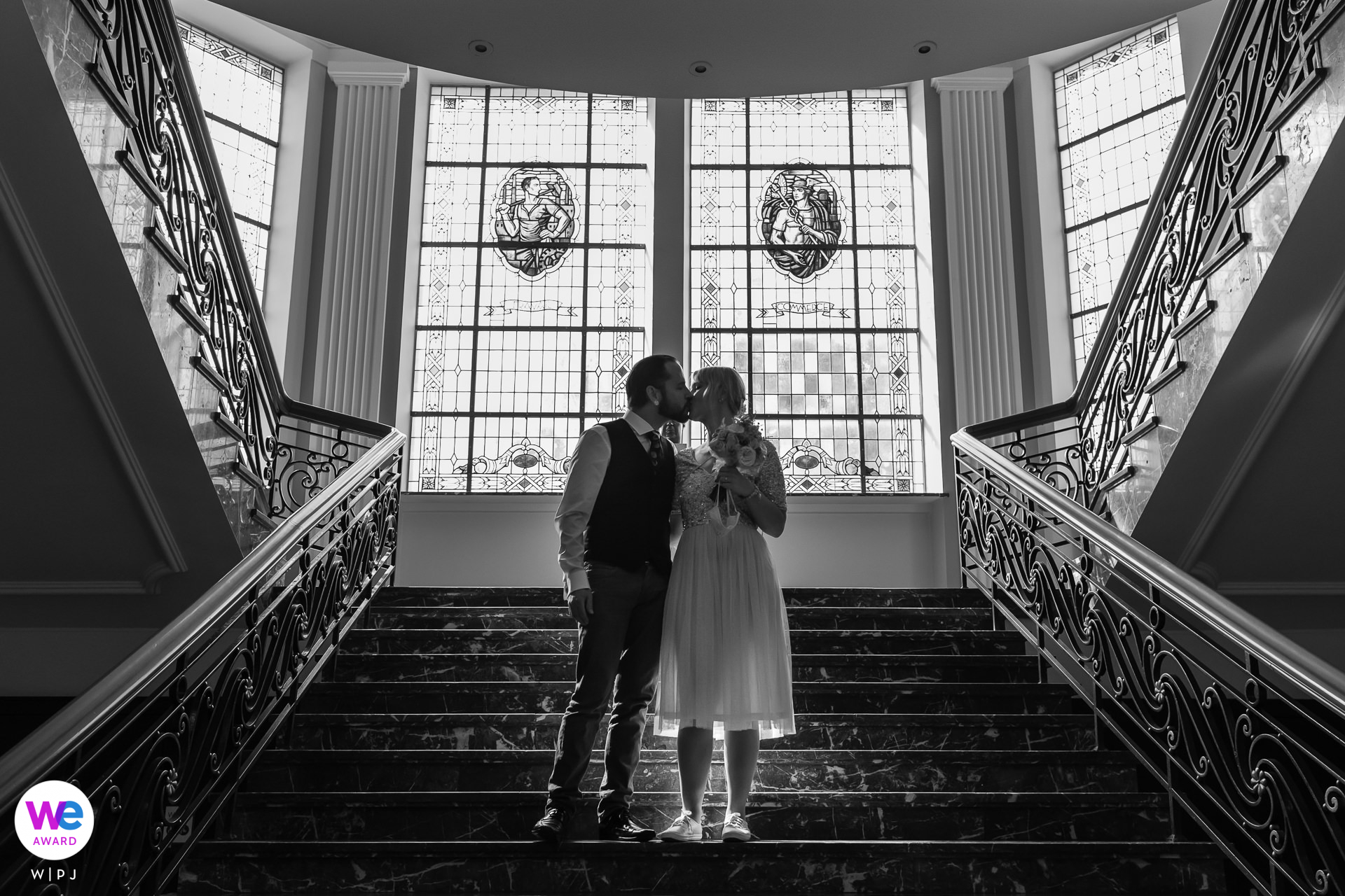 City Hall of Dudelange, Luxembourg Elopement Photography | the couple kisses on the stairs of the city hall, surrounded by bright, natural light