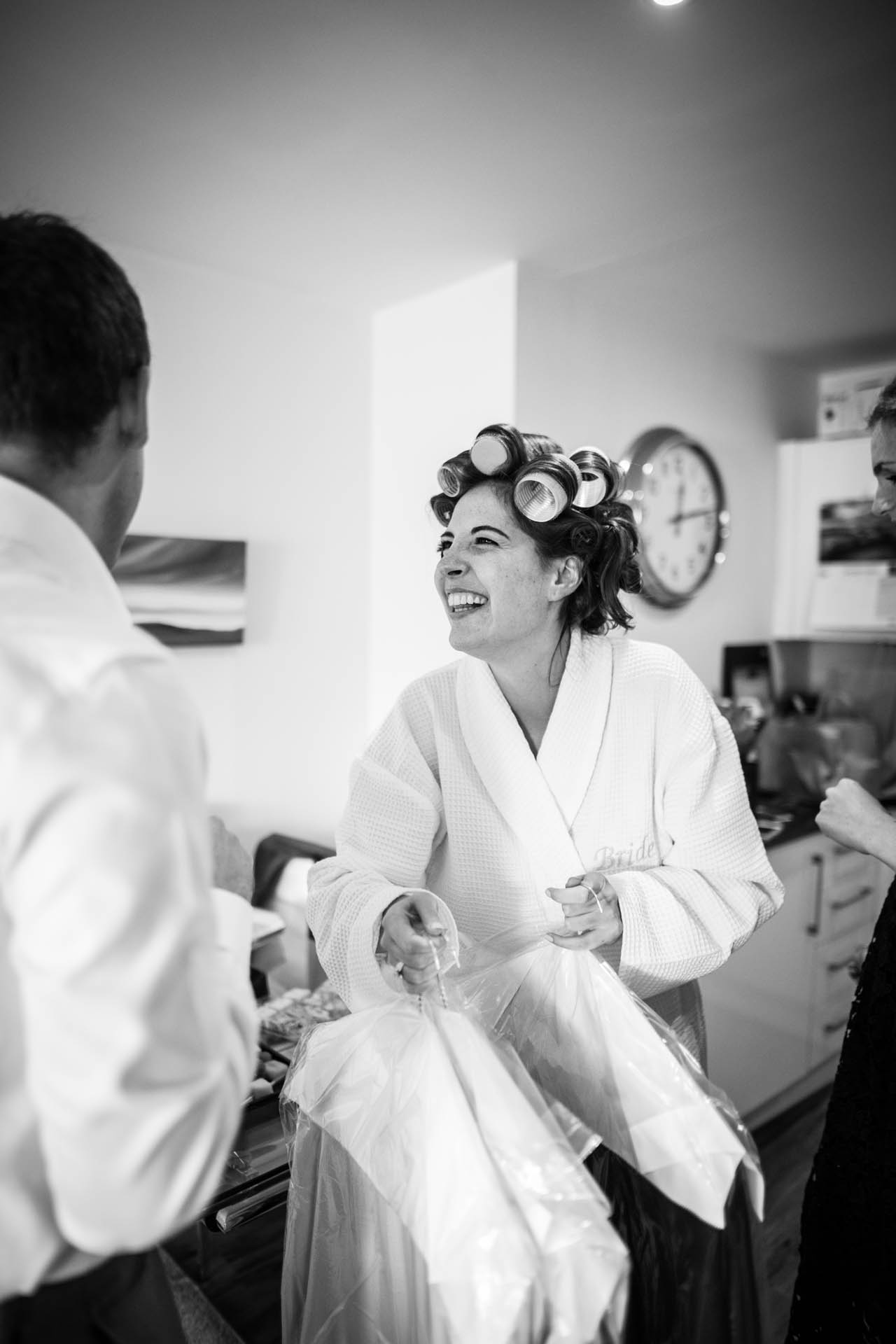 Battersea, London Elopement Image | The happy bride walks around in hair curlers