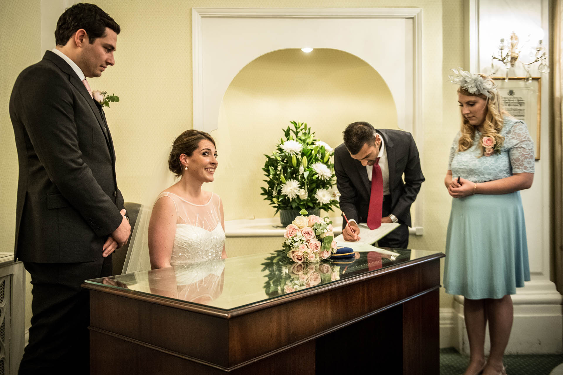 The Rossetti Room - Chelsea Old Town Hall Elopement Photos | The bride sits and waits excitedly at a desk