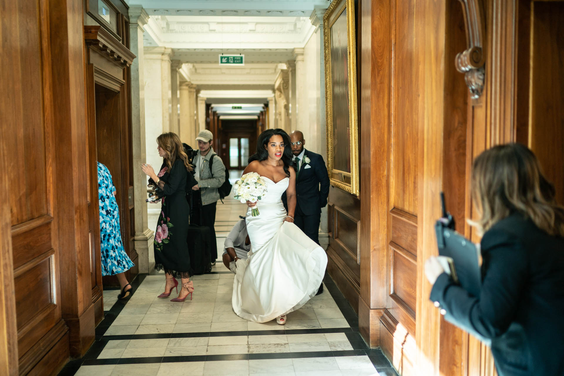 The Old Marylebone Town Hall Elopement Civil Ceremony Image | The Bride is greeted outside the Soho Room by a registrar