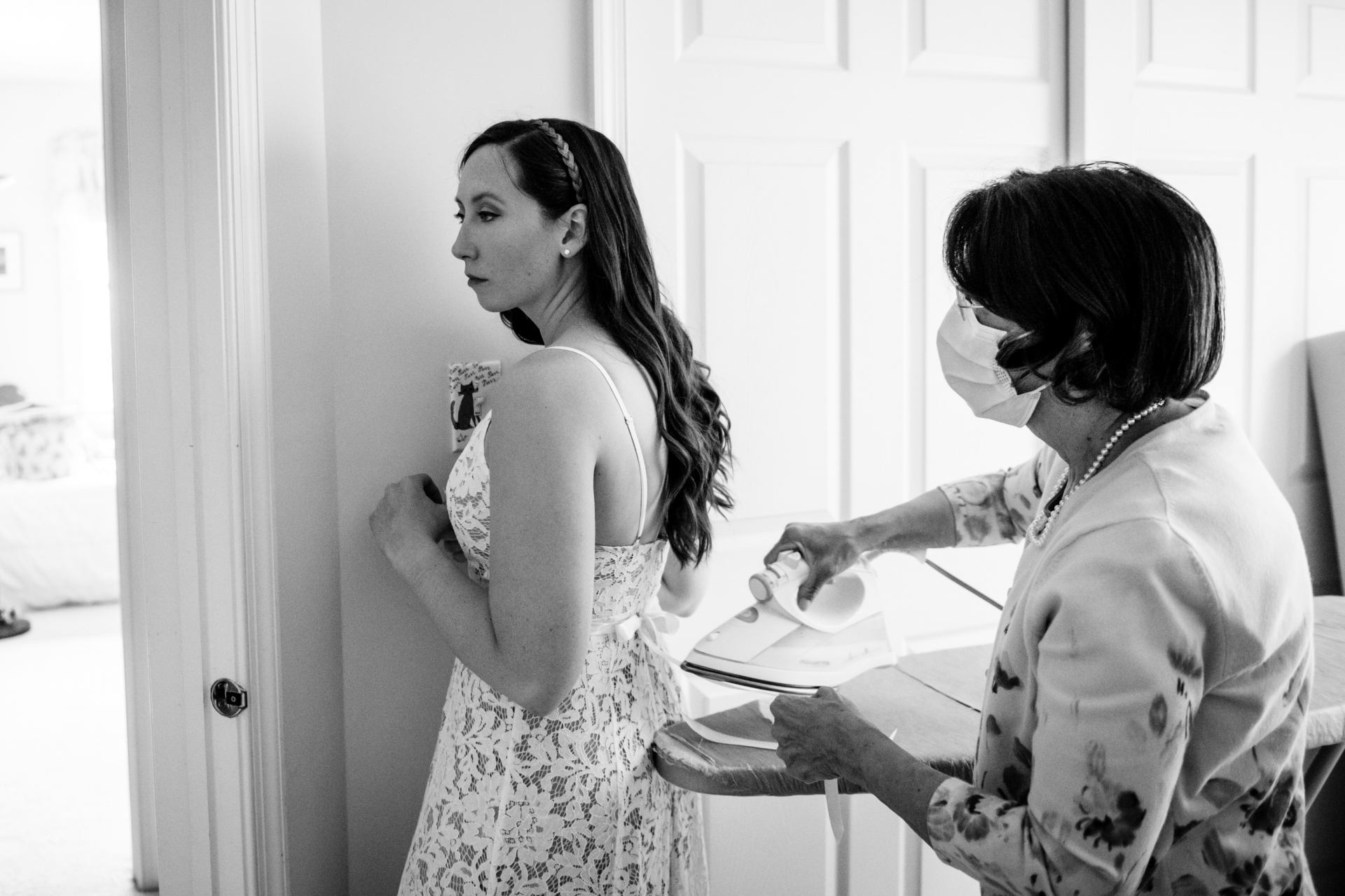 Elopement Photo of the Bride in Reston, Virginia | The bride stands against a wall as her mother irons the ribbon on her dress