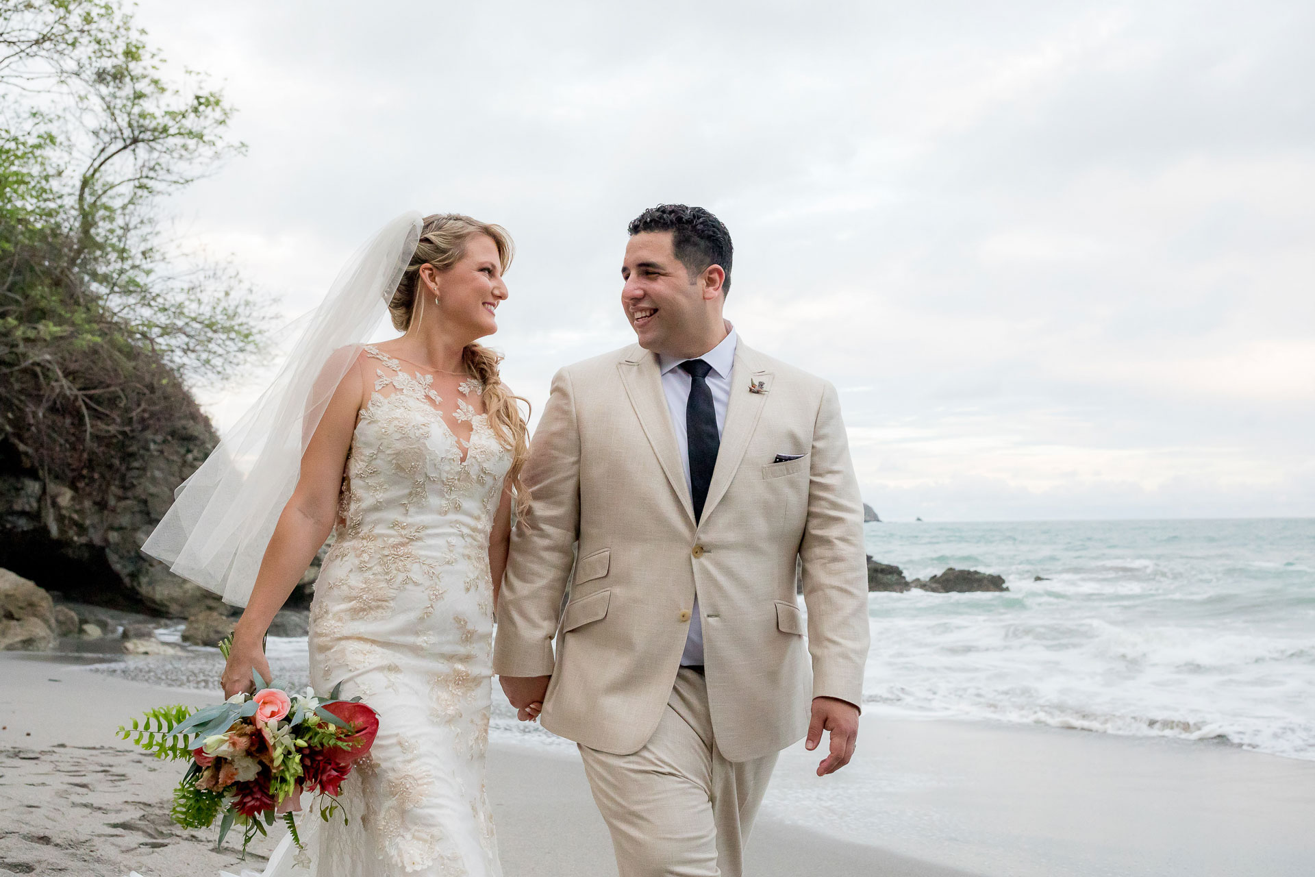 Arenas del Mar Beachfront and Rainforest Resort, Manuel Antonio, Costa Rica Elopement Image | The couple looks happily into each other's eyes as they stroll hand-in-hand