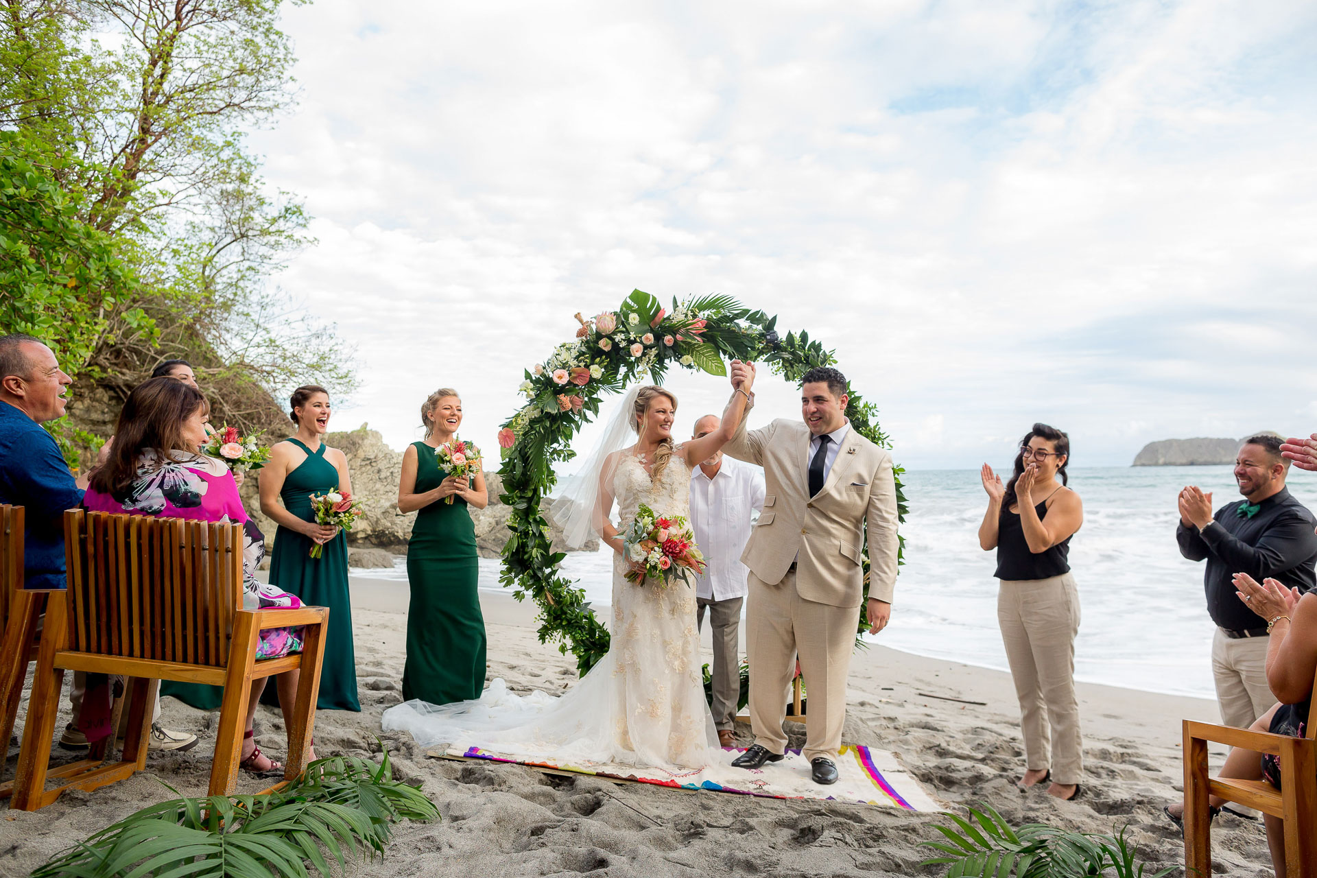 Beach elopement ceremony image - Costa Rica | As the beach ceremony ends, the newlyweds hold hands and raise them into the air