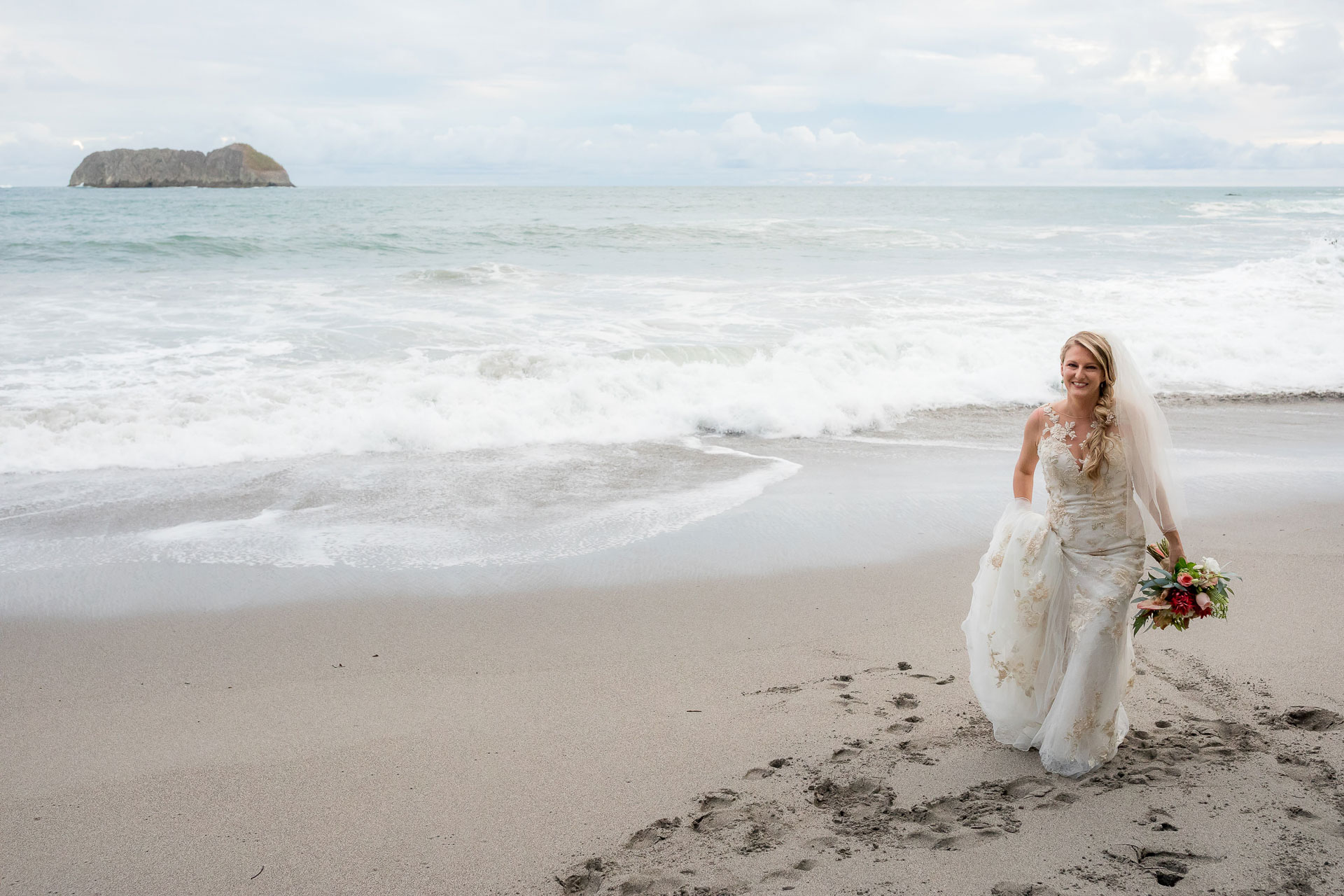 Beach elopement photography from Costa Rica | The bride walks along the beach in her wedding gown