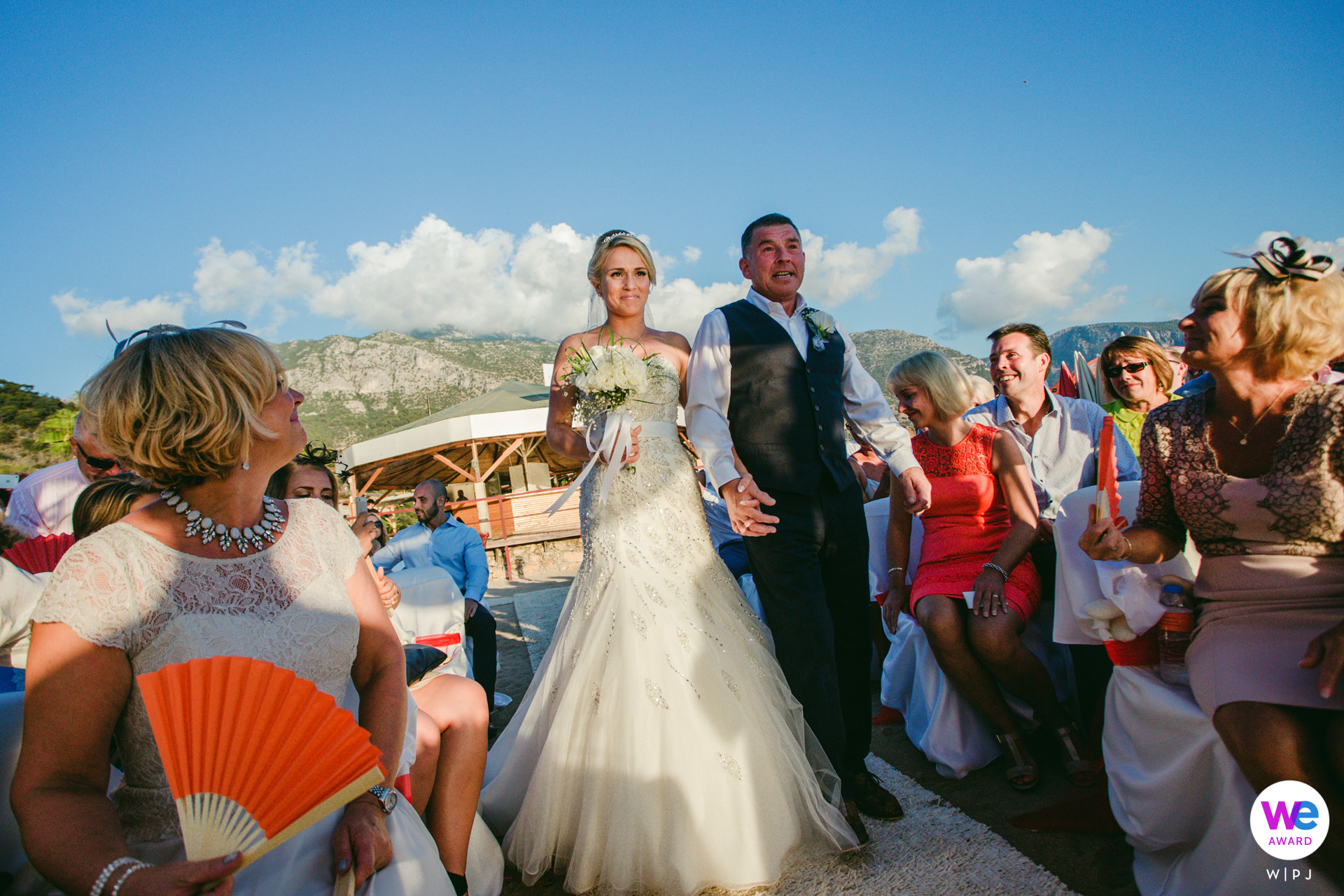 Sea Horse Beach Club, Oludeniz, Fethiye, Turkey Elopement Photos | The bride walks down the aisle with her father, surrounded on either side by their guests