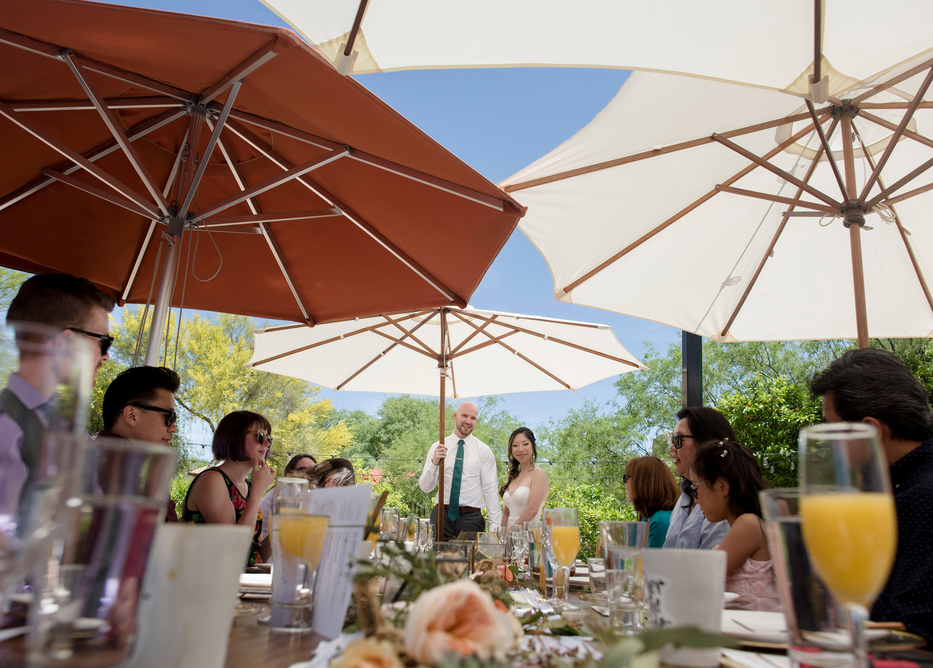 Scottsdale Elopement Reception Venue Photo | The guests are seated beneath umbrellas for the outdoor brunch reception