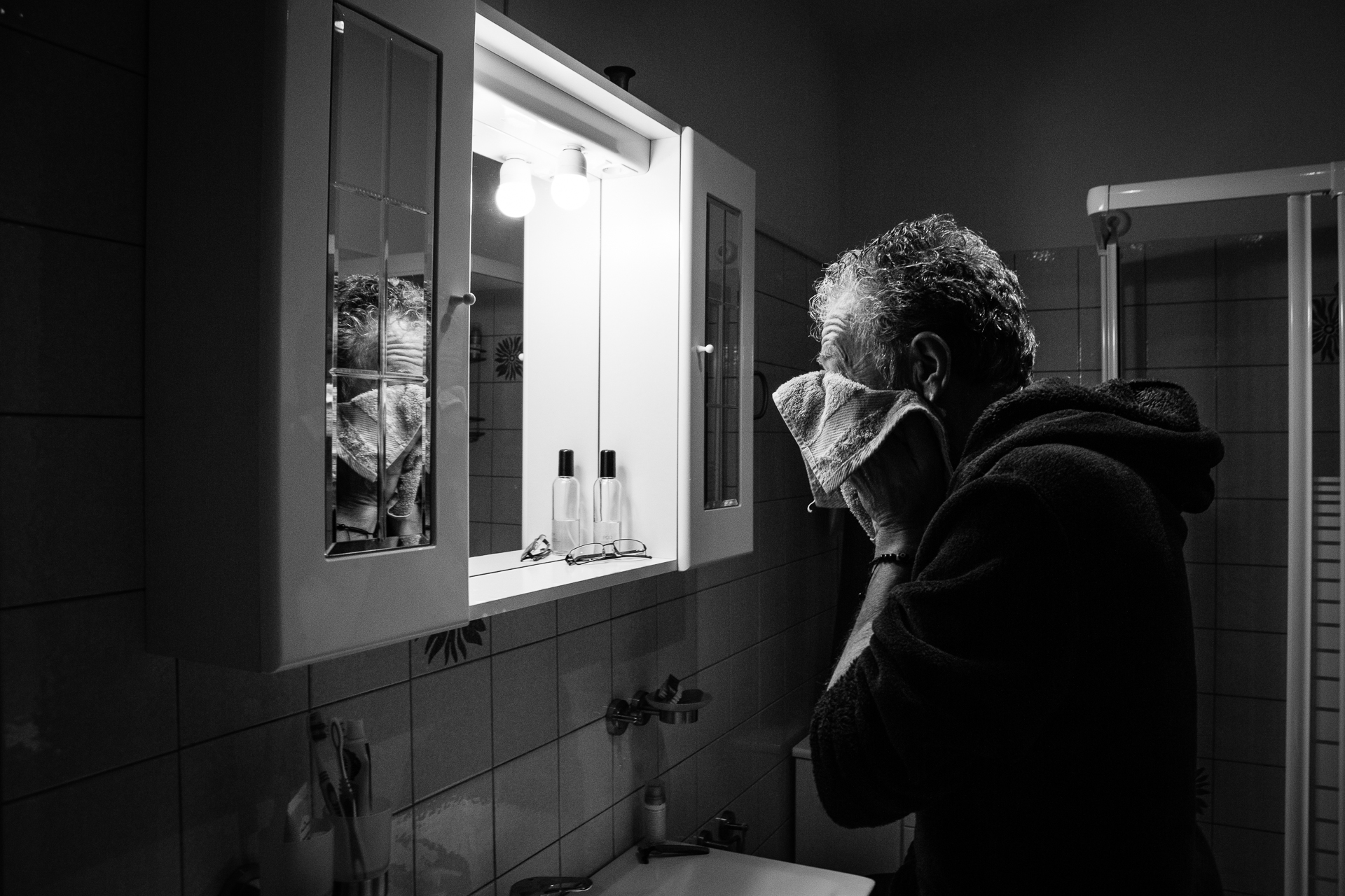 Lake of Varese, IT Elopement Image | The groom shaving in front of the bathroom mirror and pats his face dry with a towel
