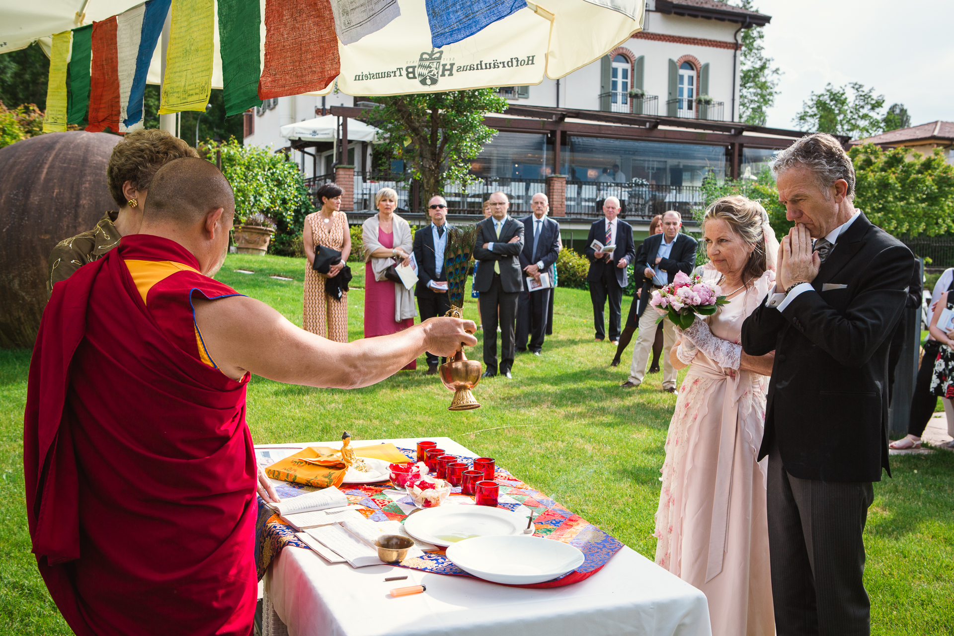 Hotel Ristorante Villa Baroni Elopement Ceremony Image | The bride and groom stand at the altar where the Buddhist monk pours oils