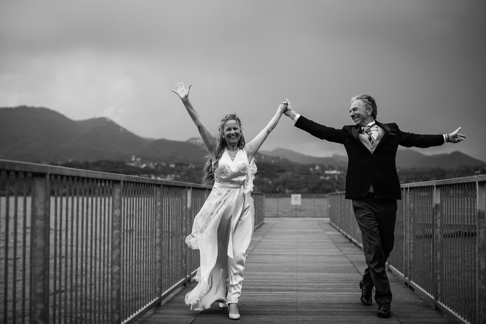 Italy Elopement Couple Portrait of the Bride and Groom at Lake Varese | The newlyweds have a bit of fun as they walk down a dock