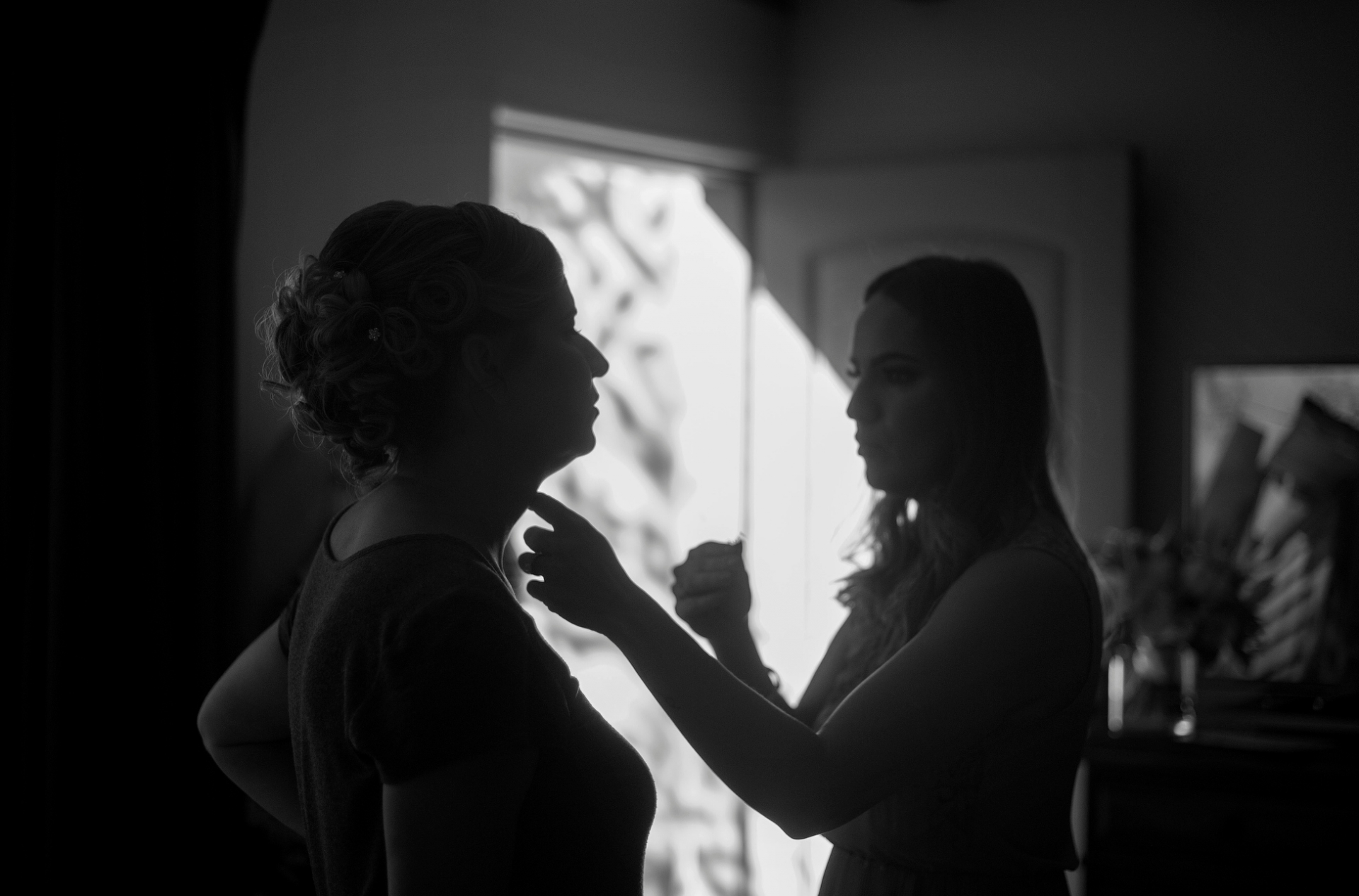 Royal Palms Resort, Phoenix, AZ Elopement Photography | the silhouette of the bride as one of her bridesmaids helps her get ready
