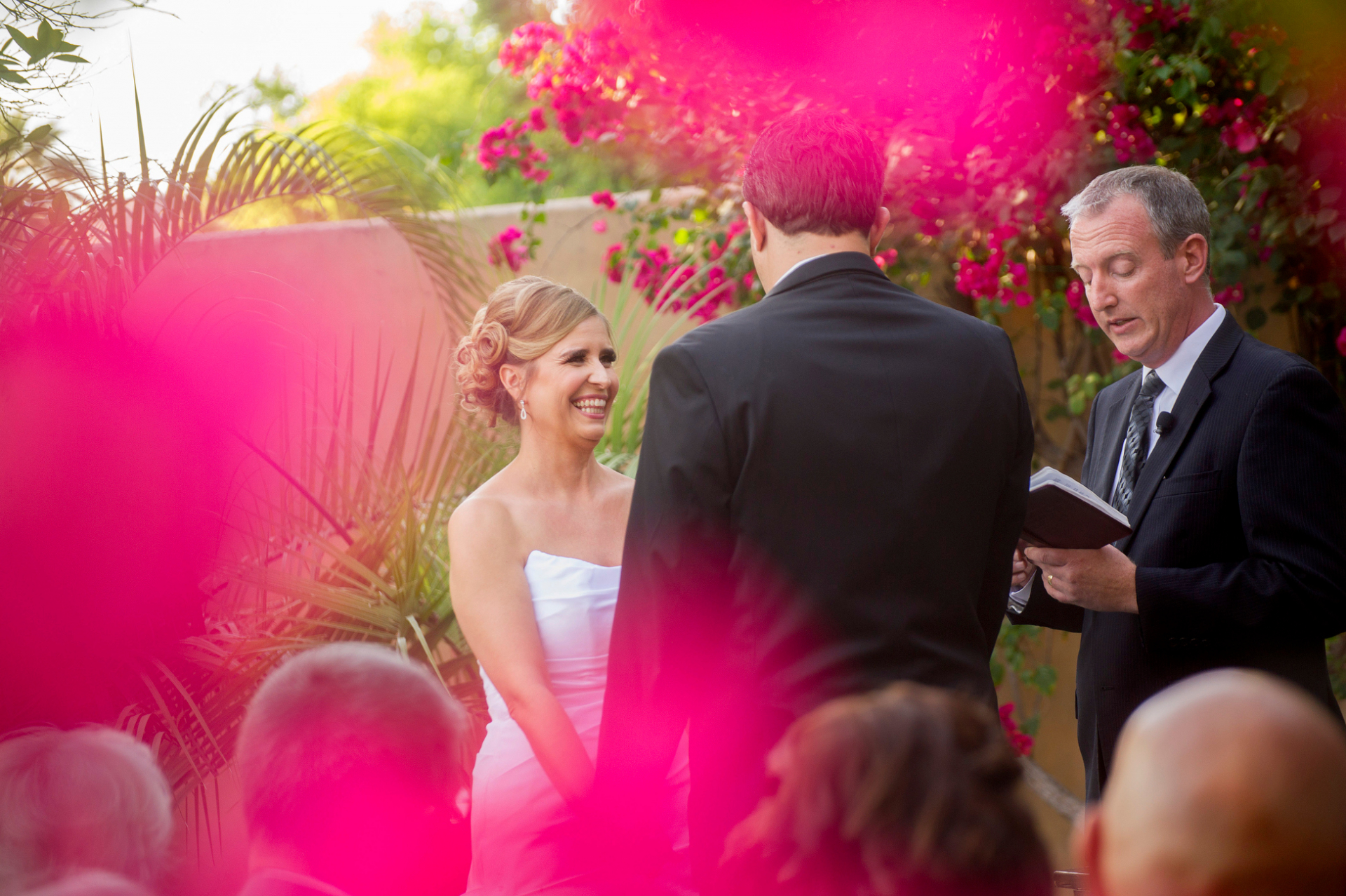 Royal Palms Resort of Arizona - Elopement Ceremony Photos | Peeking through the pink flowers surrounding the ceremony