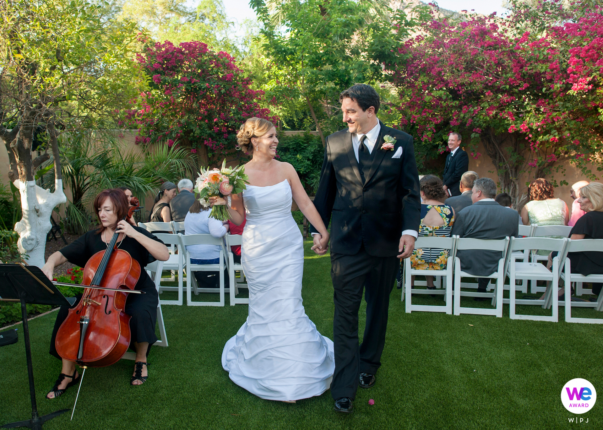Royal Palms Resort and Spa, Phoenix, Arizona Elopement Photographer | The bride and groom exit the ceremony hand-in-hand as the cellist plays them out of the lush alcove surrounded by flowers