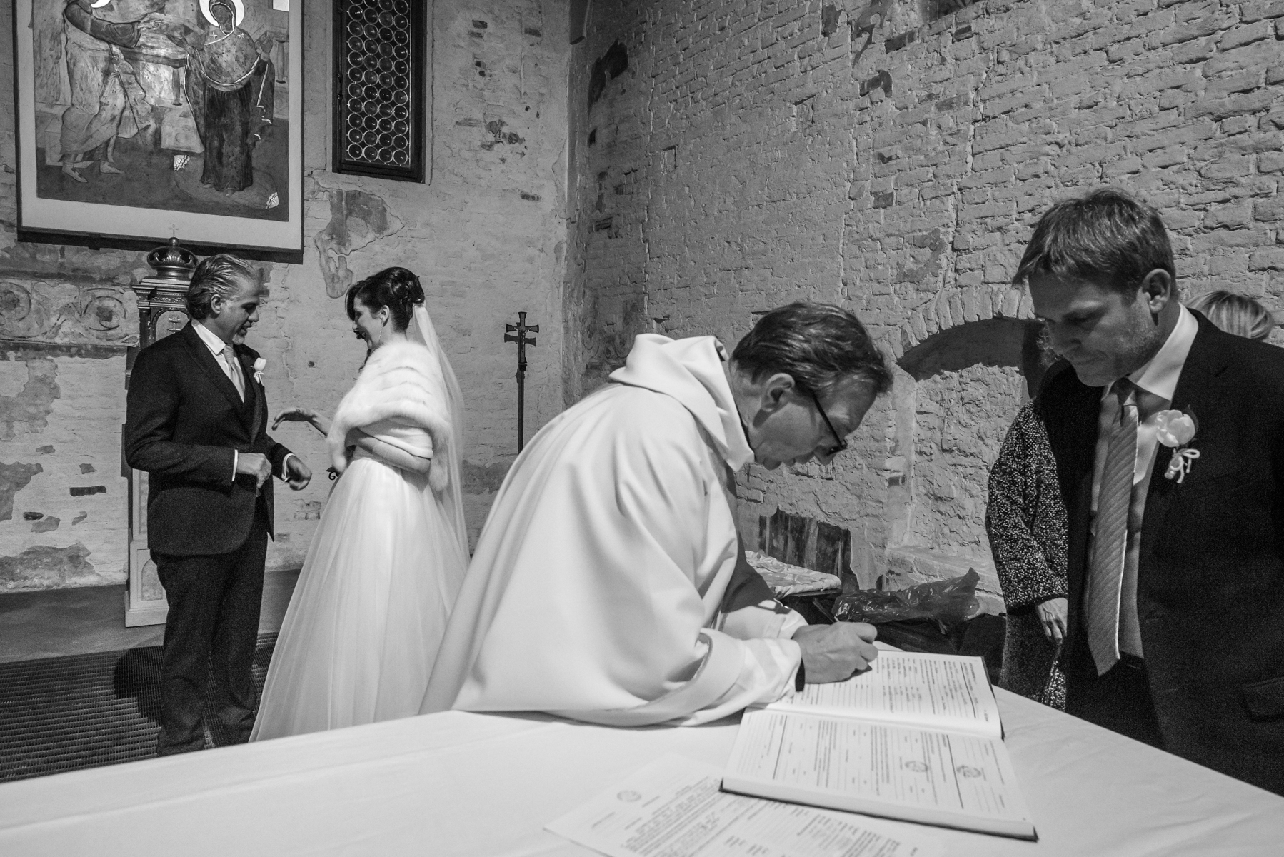Santa Maria Church, Mantua, IT Elopement Ceremony Image | the priest collects all the data of the wedding witnesses