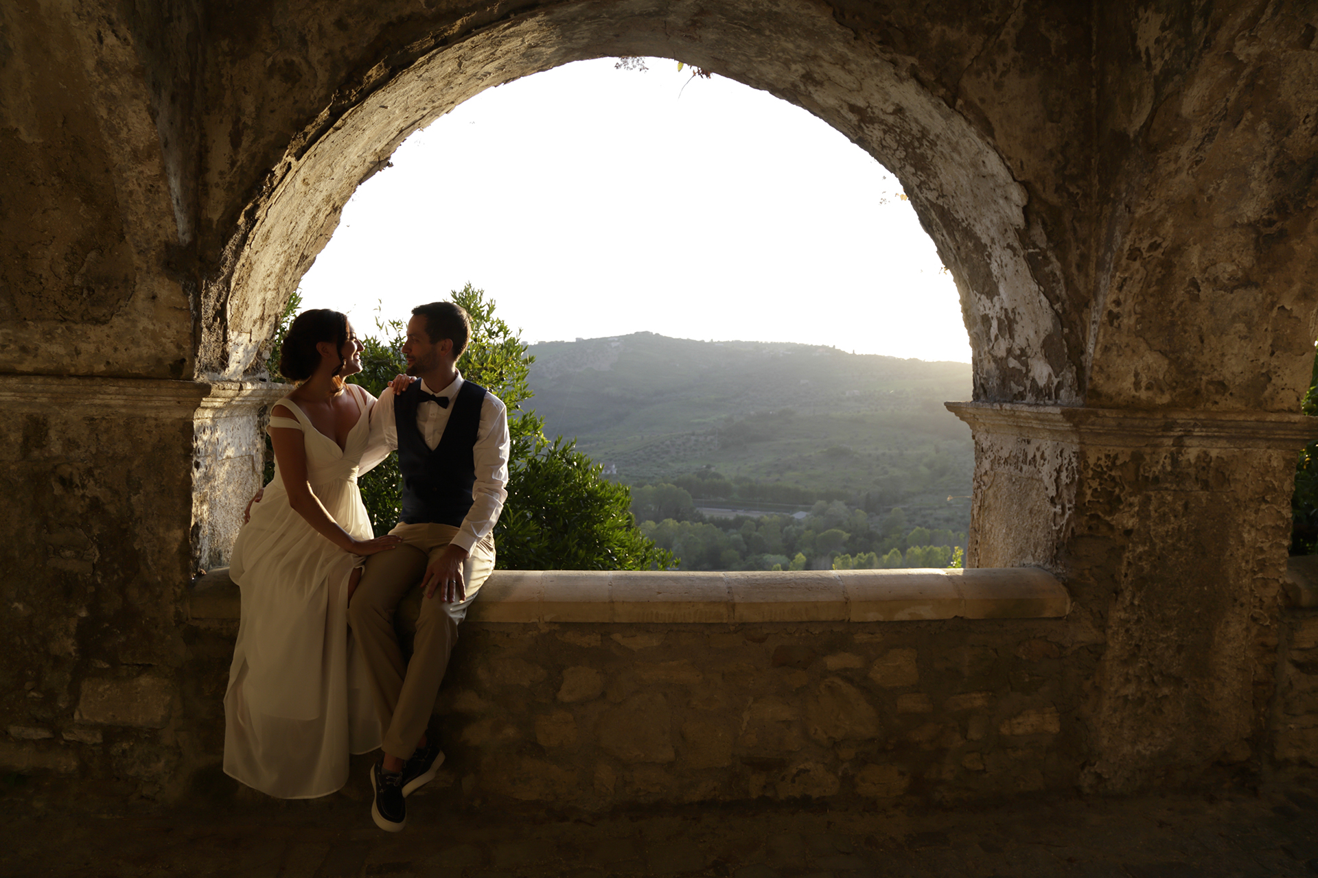 Calabria Elopement Couple Portrait | The bride and groom relaxes, enjoying the lovely sunlight