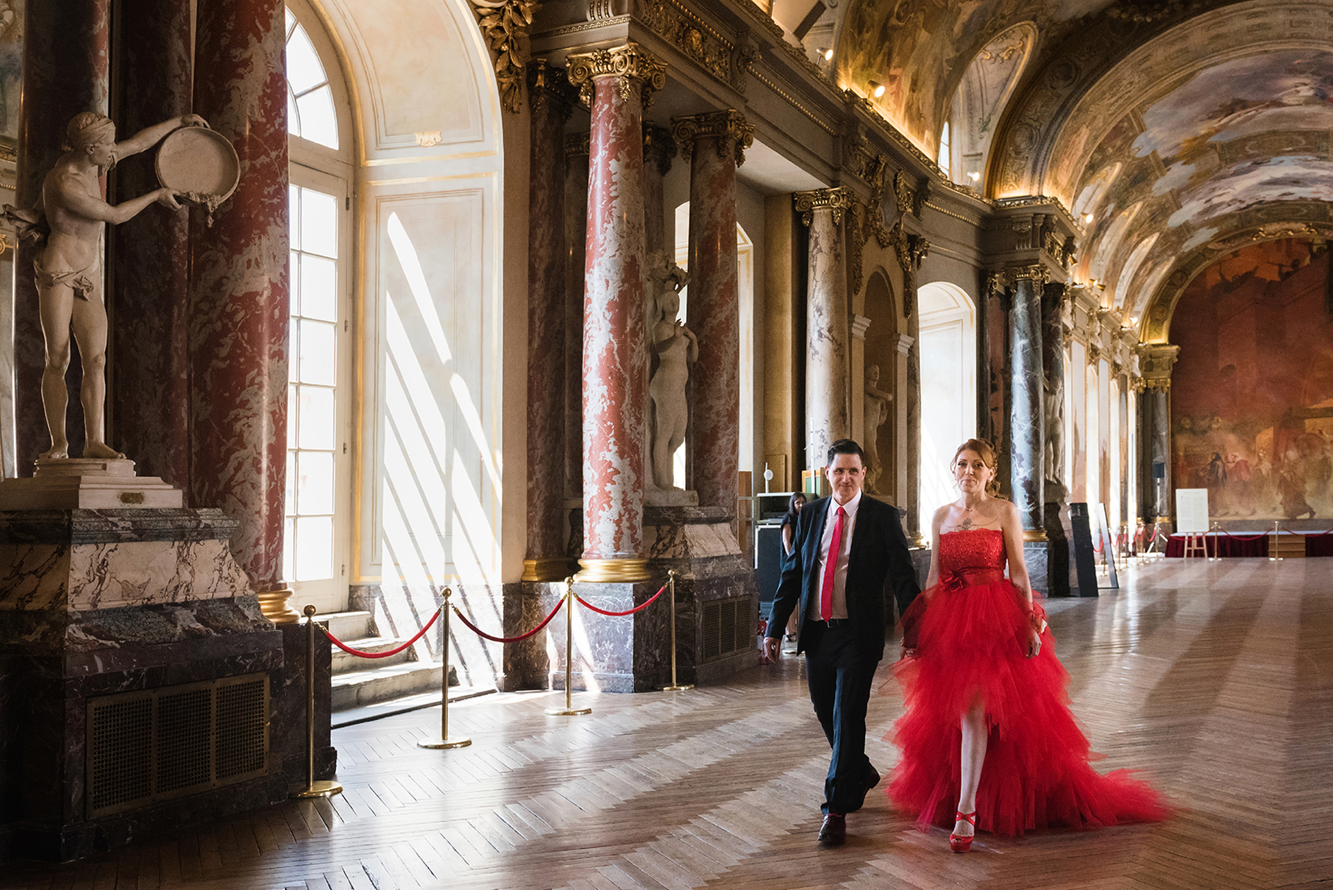 France Elopement Image from Toulouse City Hall | The bride and groom walk down a massive, ornate hallway with marble columns